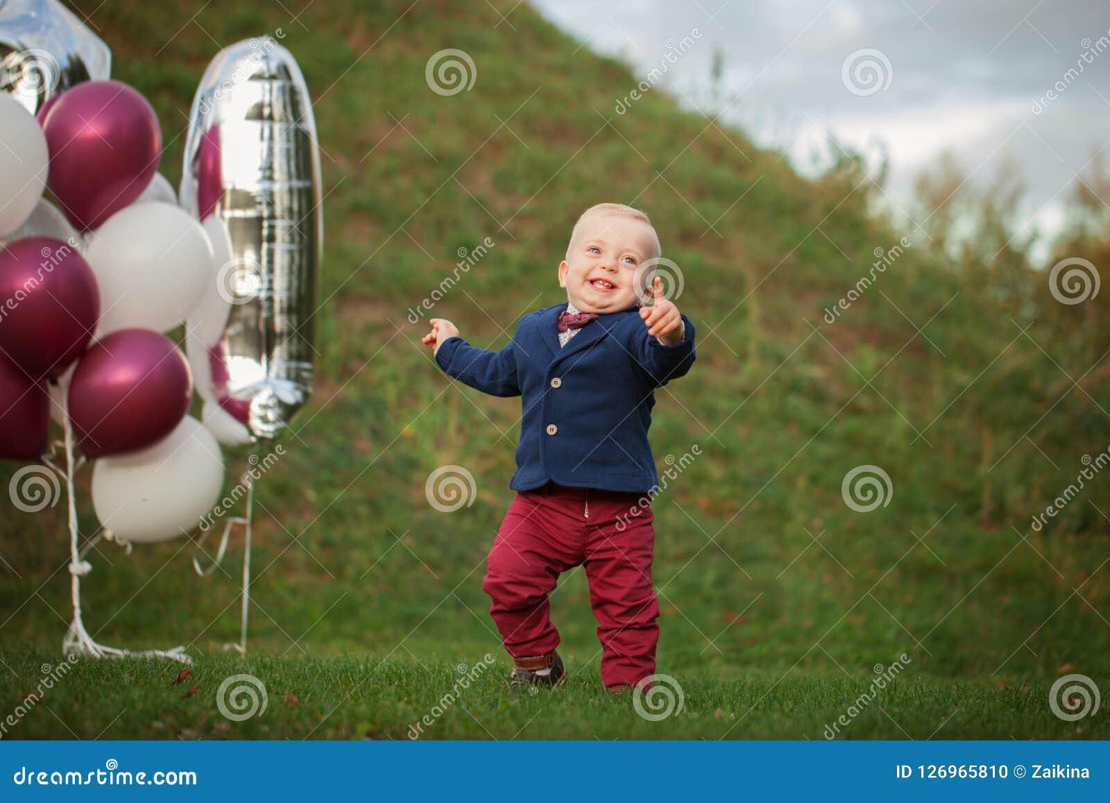 Όμορφο μωρό πορτρέτου χαμόγελου 1χρονο χαριτωμένο αγόρι στη χλόη Επέτειος γενεθλίων