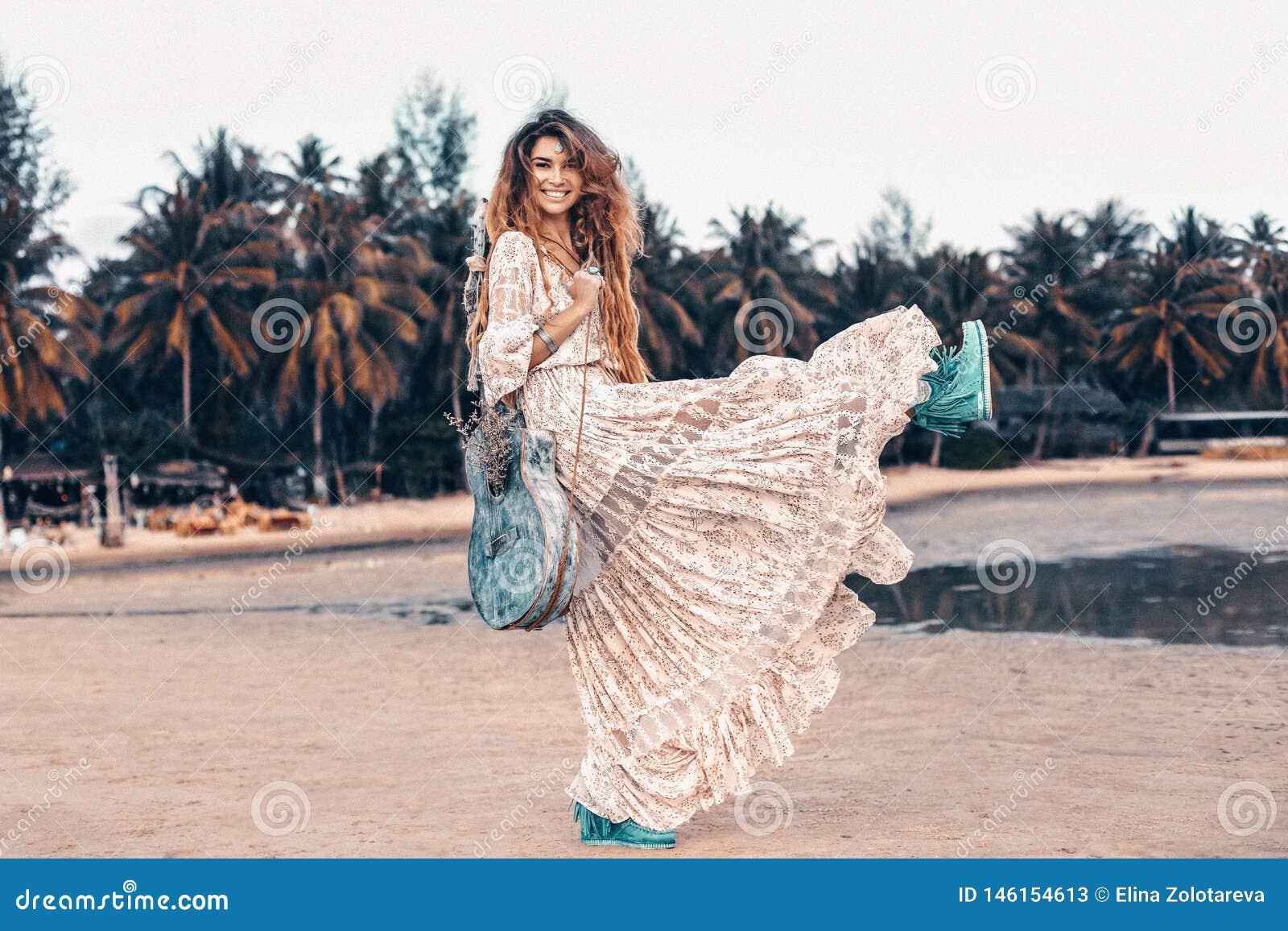 Όμορφο νέο εύθυμο πρότυπο μόδας στο άσπρο φόρεμα με την κιθάρα που έχει τη διασκέδαση υπαίθρια στο ηλιοβασίλεμα