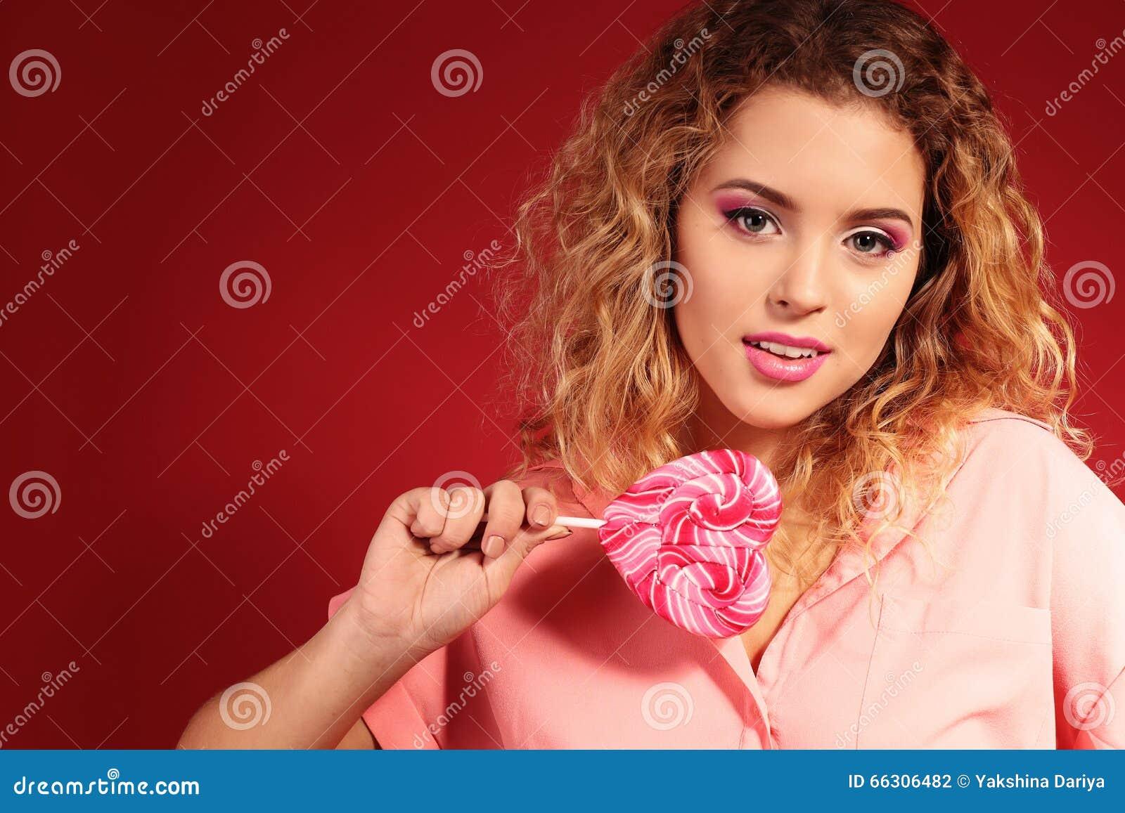 da034e73ef1 Φωτογραφία στούντιο μόδας του όμορφου νέου κοριτσιού με την ξανθή σγουρή  τρίχα και το βράδυ makeup, με την καραμέλα στη μορφή καρδιών