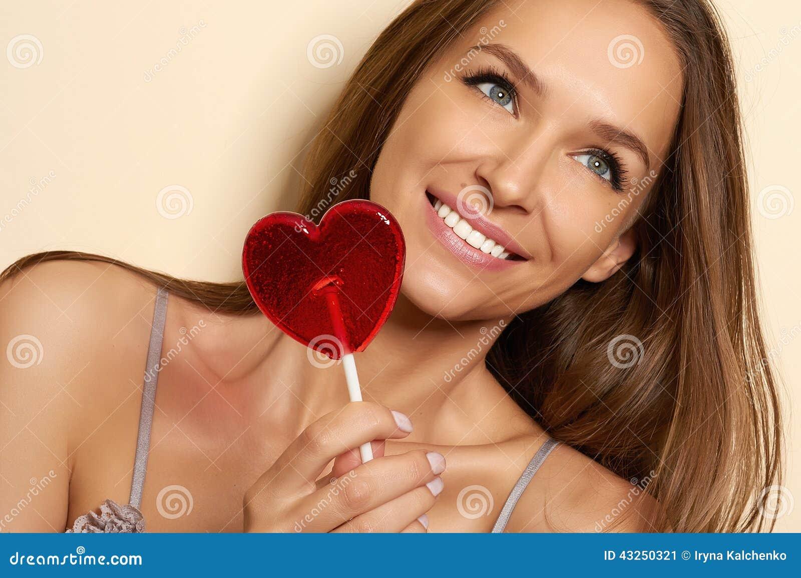 Όμορφο νέο κορίτσι σε μια εσθήτα επιδέσμου του μεταξιού και της δαντέλλας με τα λεπτά λουριά μακαρονιών με την περικοπή και τόξο