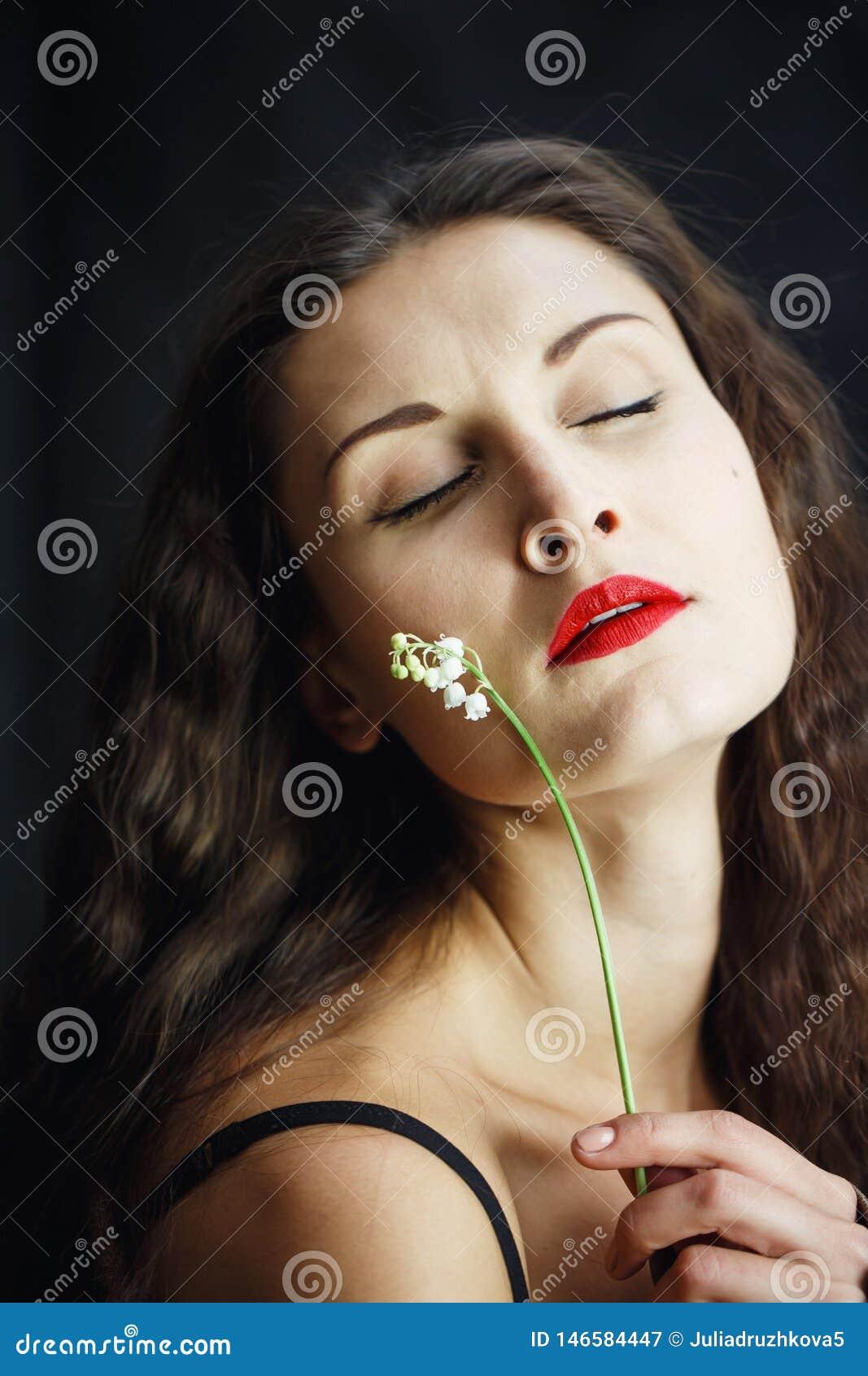 Όμορφο νέο κορίτσι στην τοποθέτηση σακακιών δέρματος στο στούντιο απομονωμένο στο ο Μαύρος υπόβαθρο Στα χέρια του λουλουδιού γυνα