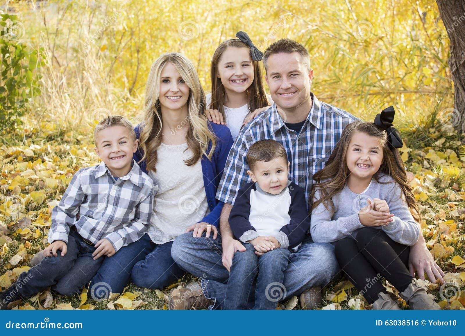 Όμορφο νέο οικογενειακό πορτρέτο με τα χρώματα πτώσης στο υπόβαθρο