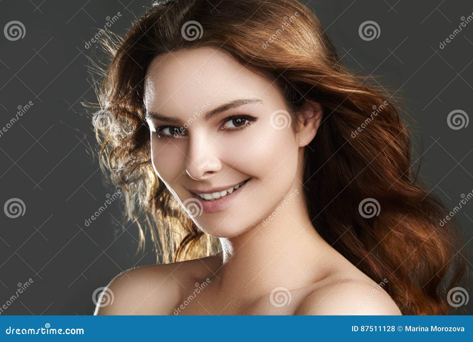 Όμορφο νέο πρότυπο γυναικών με την πετώντας καφετιά τρίχα Ομορφιά με το καθαρό δέρμα, μόδα makeup Αποτελέστε, σγουρό hairstyle