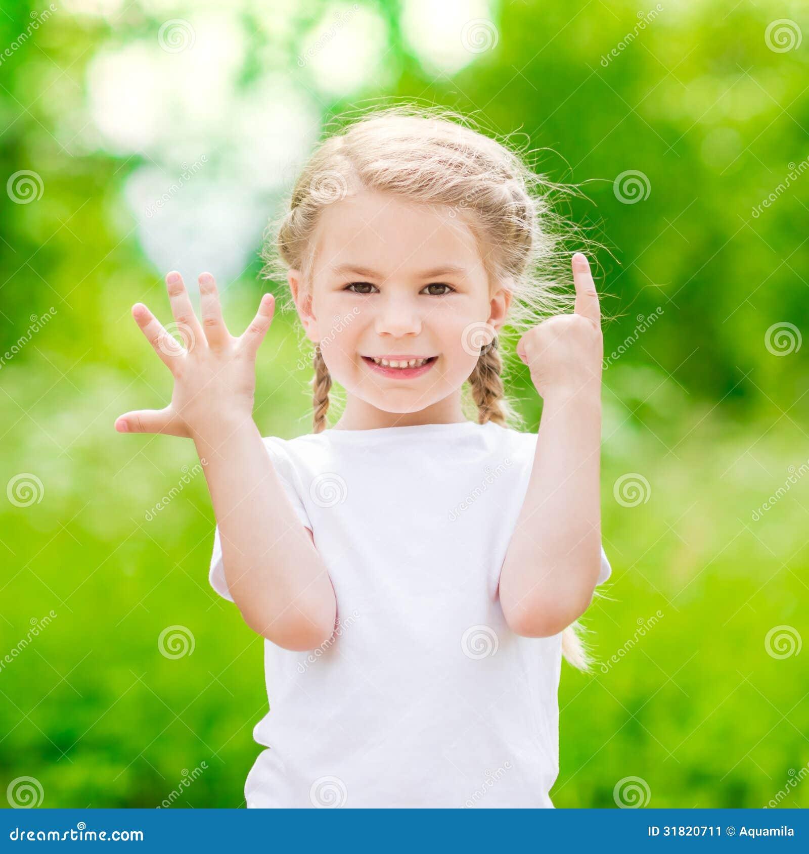 Όμορφο ξανθό μικρό κορίτσι που παρουσιάζει έξι δάχτυλα (η ηλικία της)