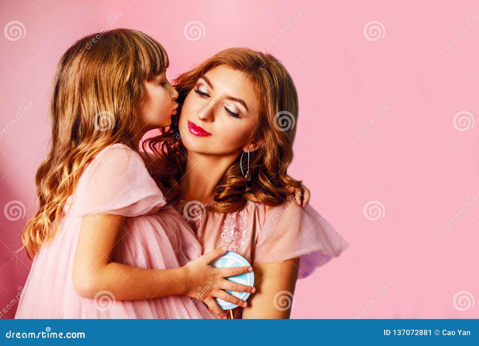 Όμορφο ξανθό mom με τη χαριτωμένη κόρη στο ρόδινο υπόβαθρο στο στούντιο Η ημέρα της ευτυχούς μητέρας, κόρη αγκαλιάζει mom και φιλ