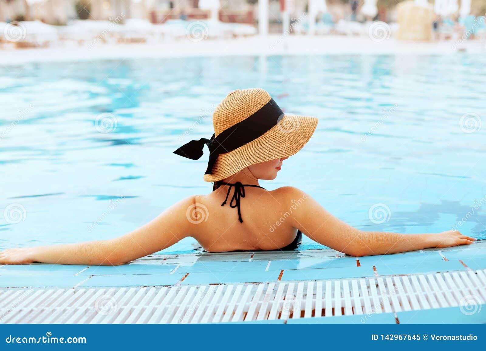 Προσοχή σώματος θερινών γυναικών Όμορφο προκλητικό κορίτσι με το υγιές δέρμα στο κομψό ριγωτό μπικίνι, χαλάρωση καπέλων ήλιων στη