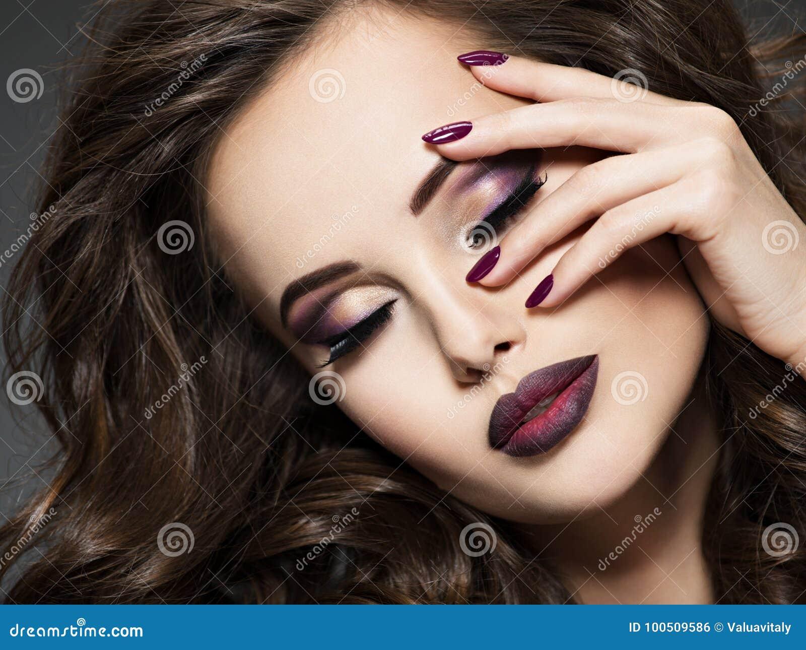Όμορφο πρόσωπο της γυναίκας με το καφέ makeup και τα καρφιά