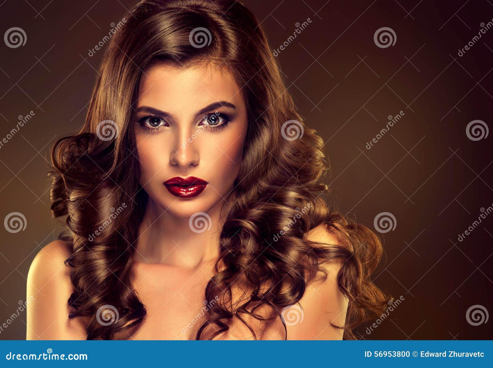 Όμορφο πρότυπο κοριτσιών με τη μακριά καφετιά κατσαρωμένη τρίχα