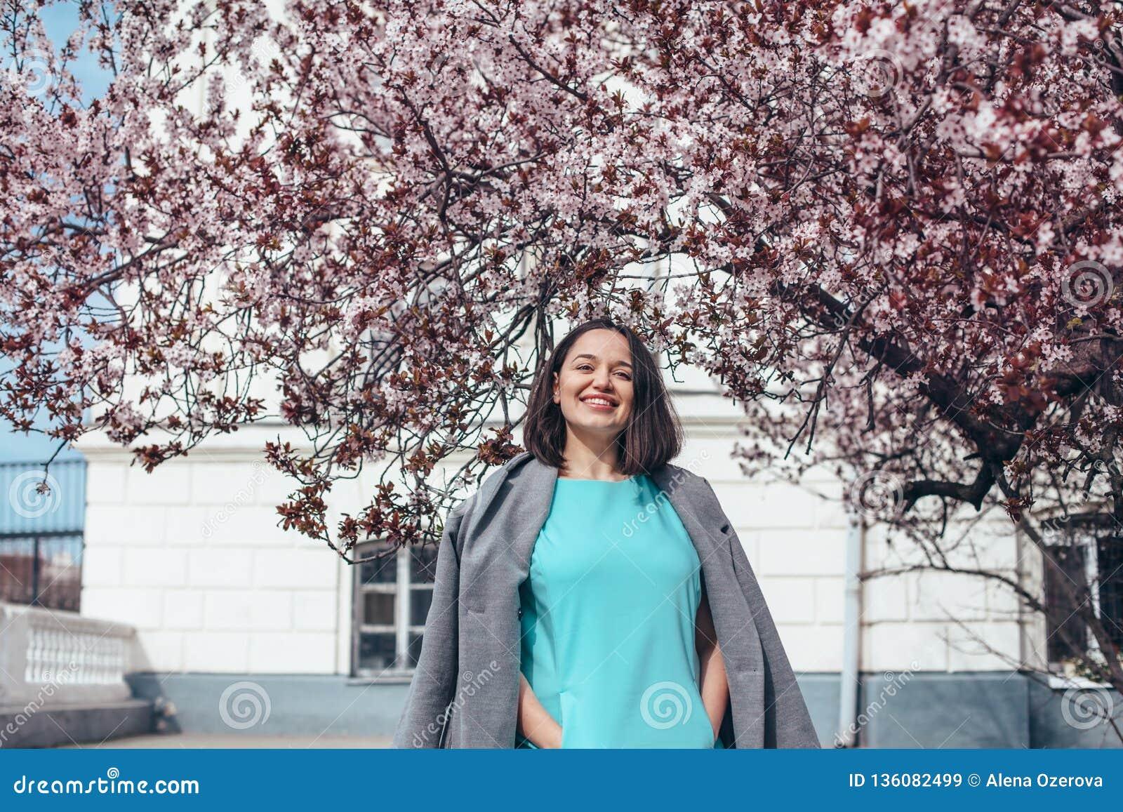 Όμορφο πρότυπο στο μπλε φόρεμα και γκρίζο παλτό από το ανθίζοντας δέντρο άνοιξη