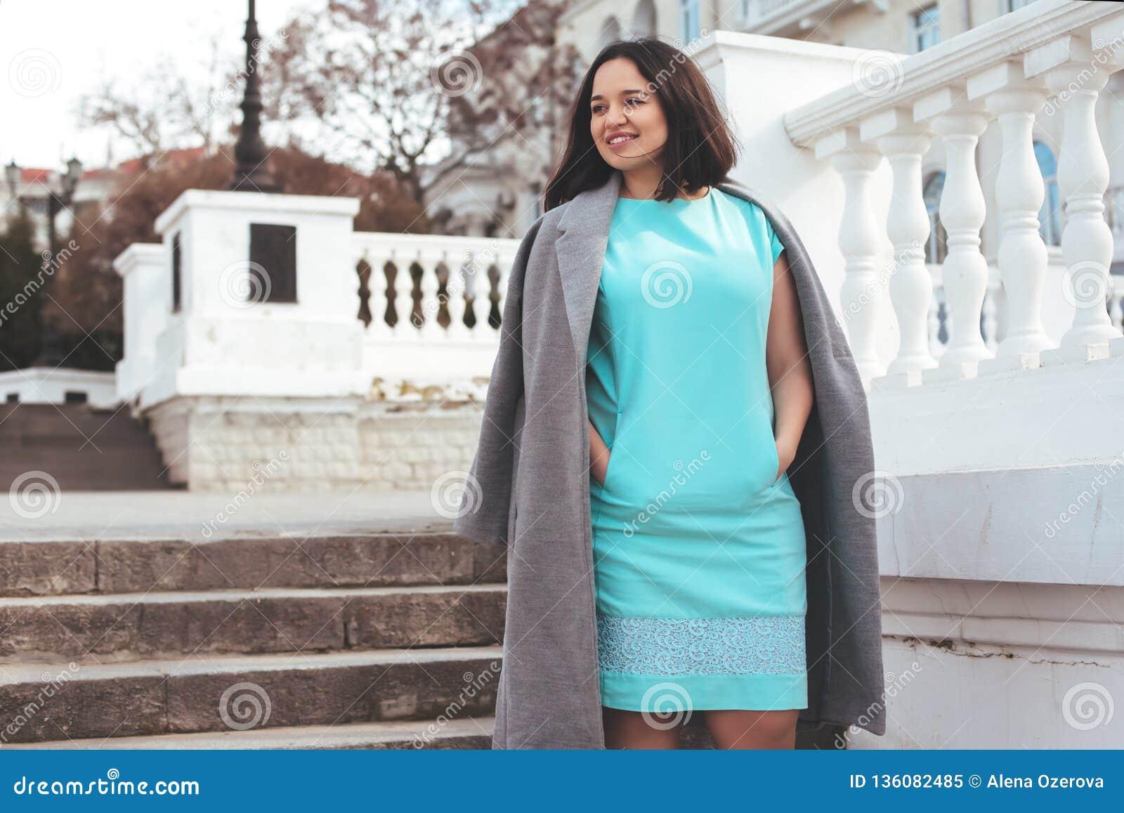 Όμορφο πρότυπο στο μπλε φόρεμα και γκρίζο παλτό στην οδό πόλεων
