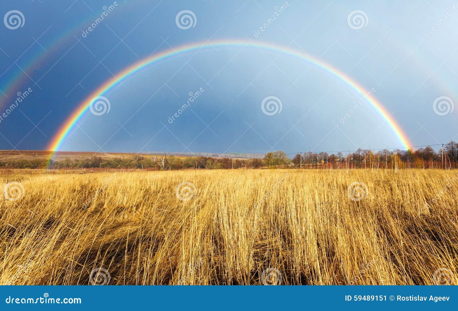 Όμορφο πλήρες ουράνιο τόξο επάνω από τον αγροτικό τομέα στην άνοιξη