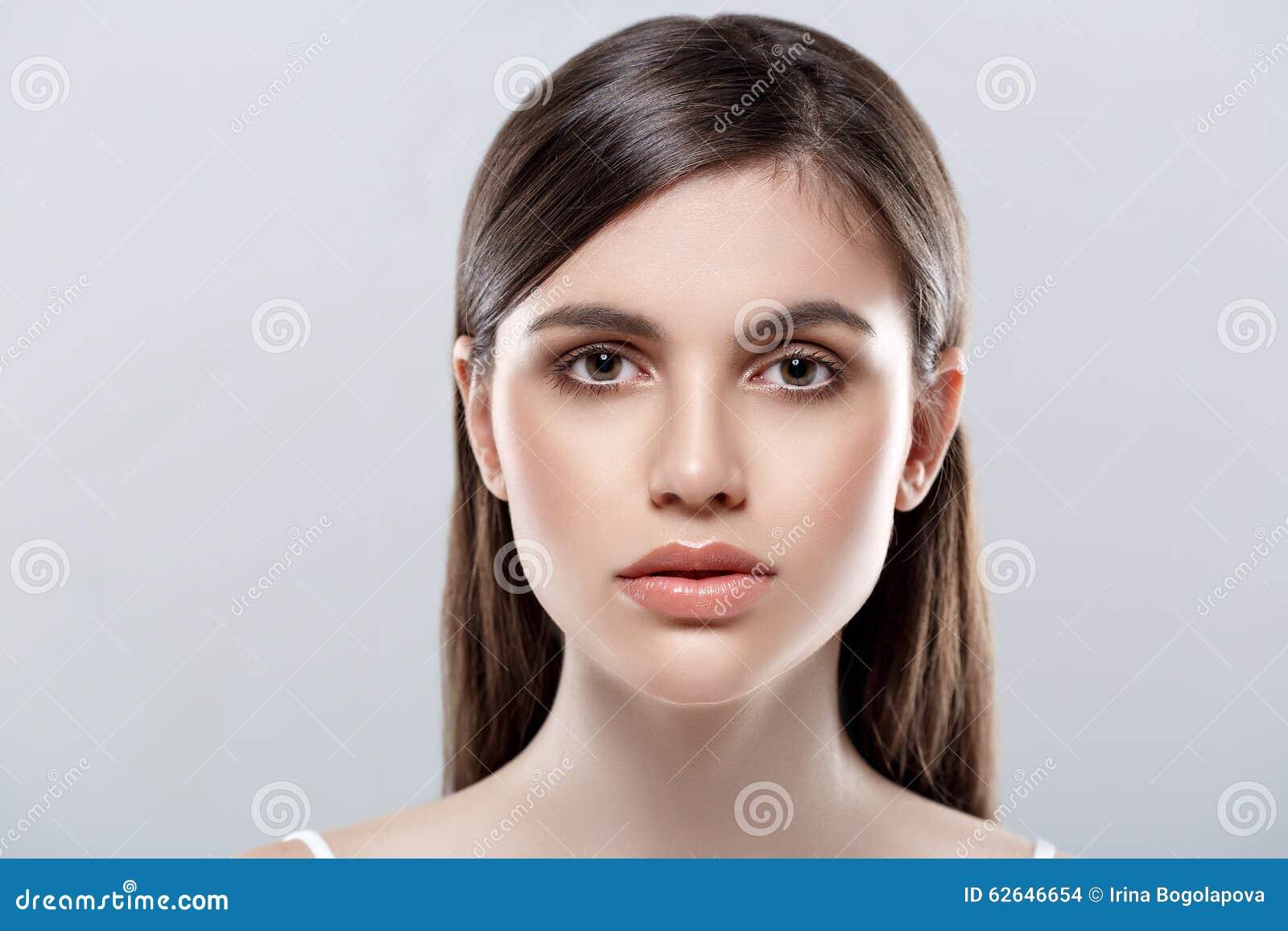 Όμορφο στούντιο προσώπου γυναικών στο λευκό με τα προκλητικά χείλια στο γκρίζο υπόβαθρο