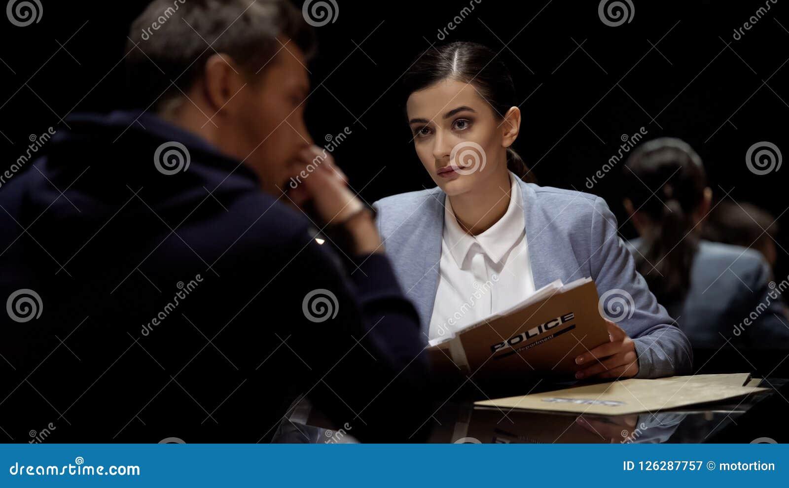 Όμορφο συλλήφθείτ συνεδρίαση άτομο ανακρίσεων, έγκλημα έρευνας, δυσπιστία