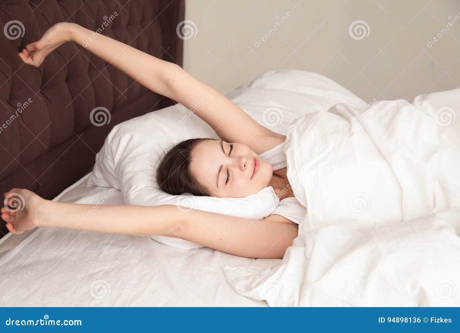 Όμορφο τέντωμα γυναικών με την ευχαρίστηση στο κρεβάτι