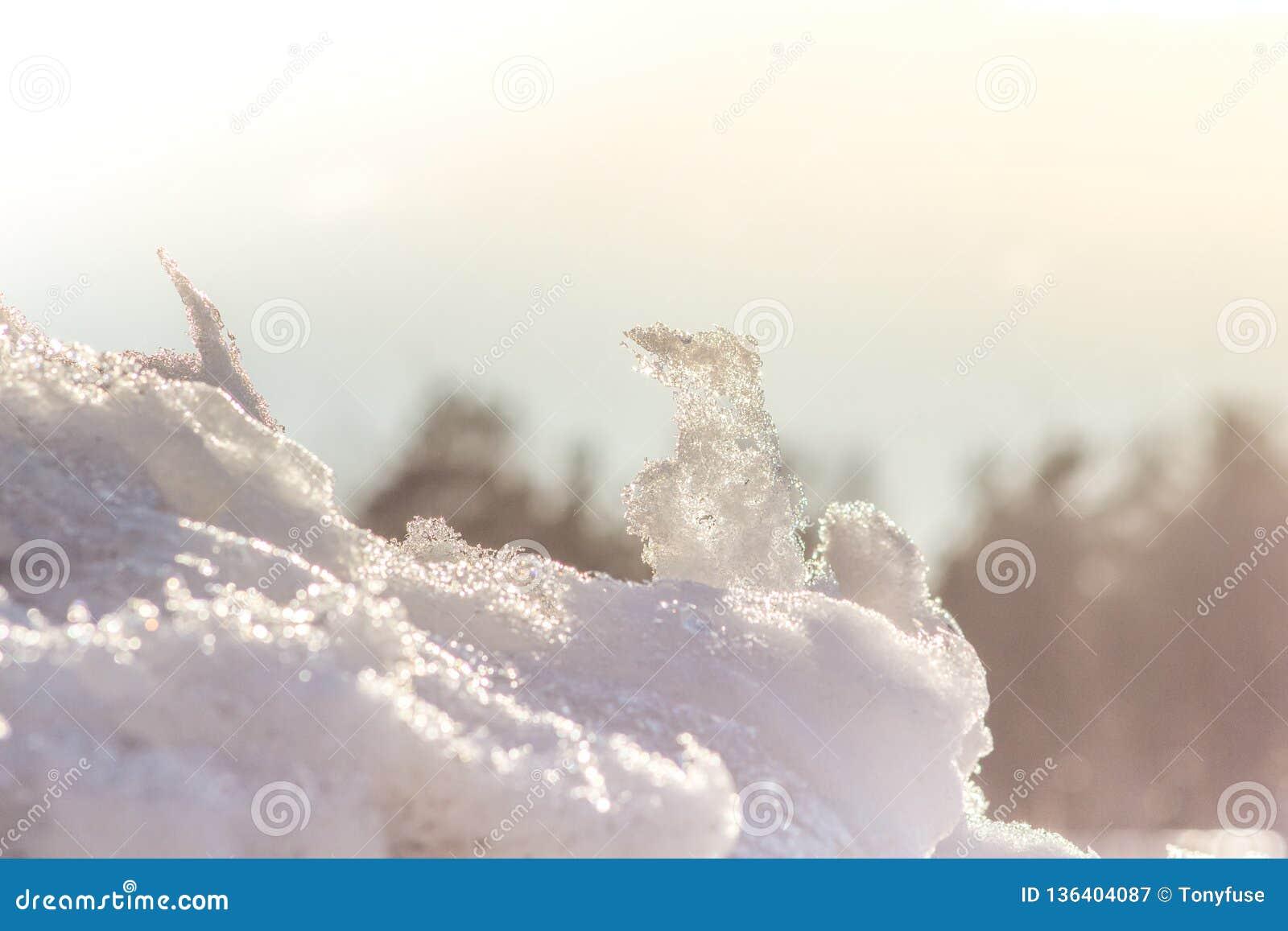 Όμορφο υπόβαθρο των χιονωδών ακτίνων ήλιων λόφων την άνοιξη