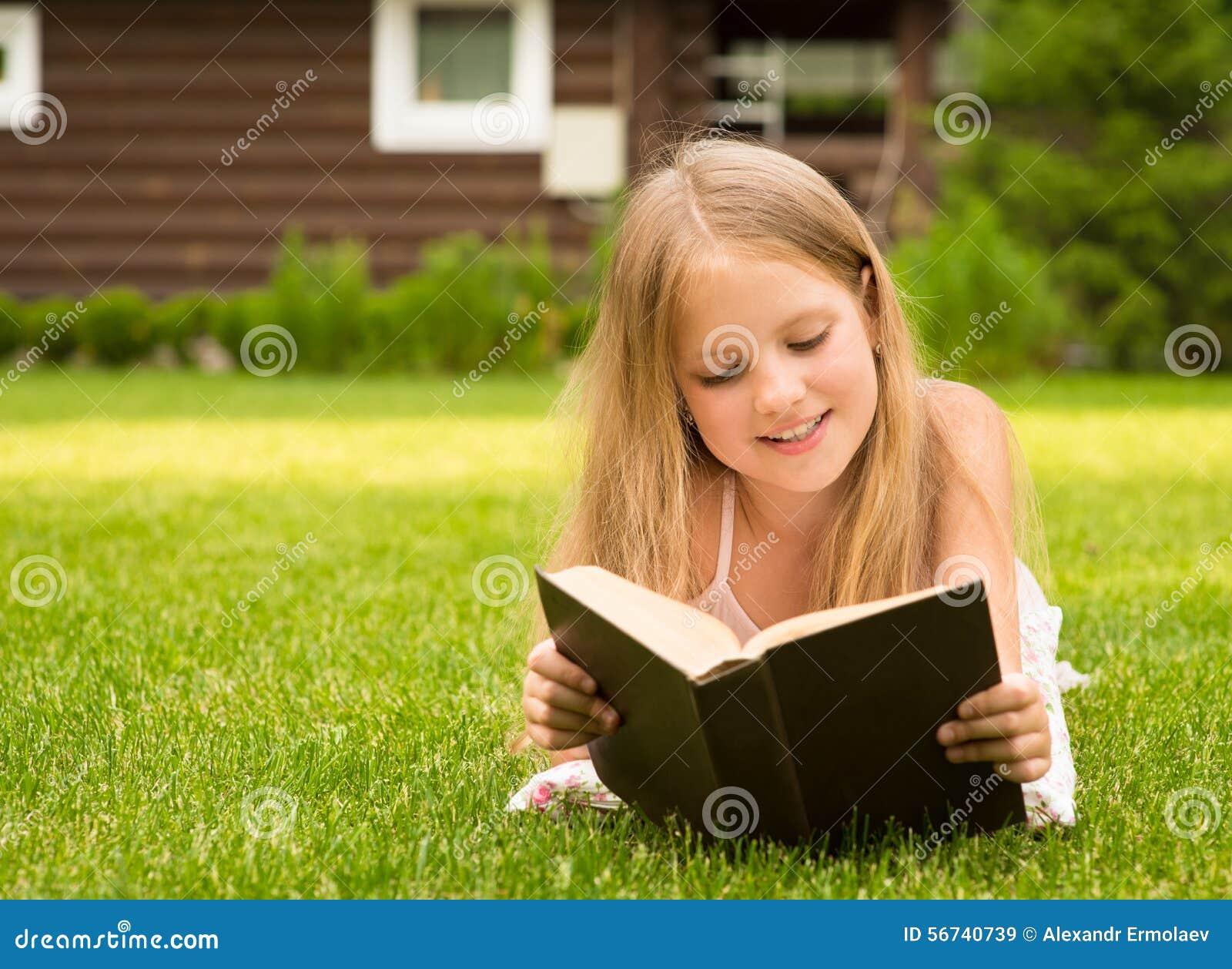 Όμορφο χαμογελώντας έφηβη που βρίσκεται στη χλόη και το διαβασμένο βιβλίο