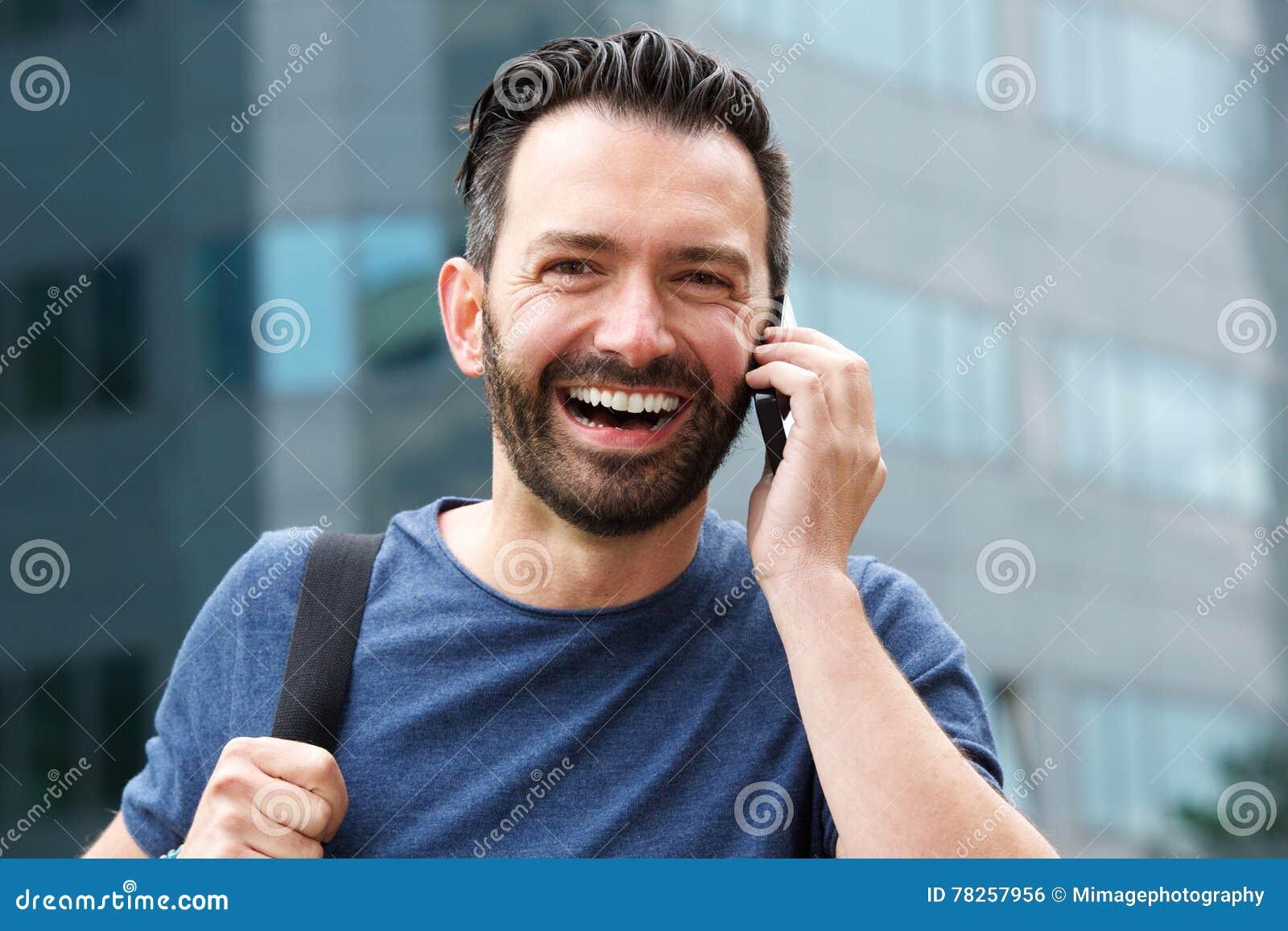 Όμορφο ώριμο άτομο που χρησιμοποιεί το τηλέφωνο και το γέλιο κυττάρων