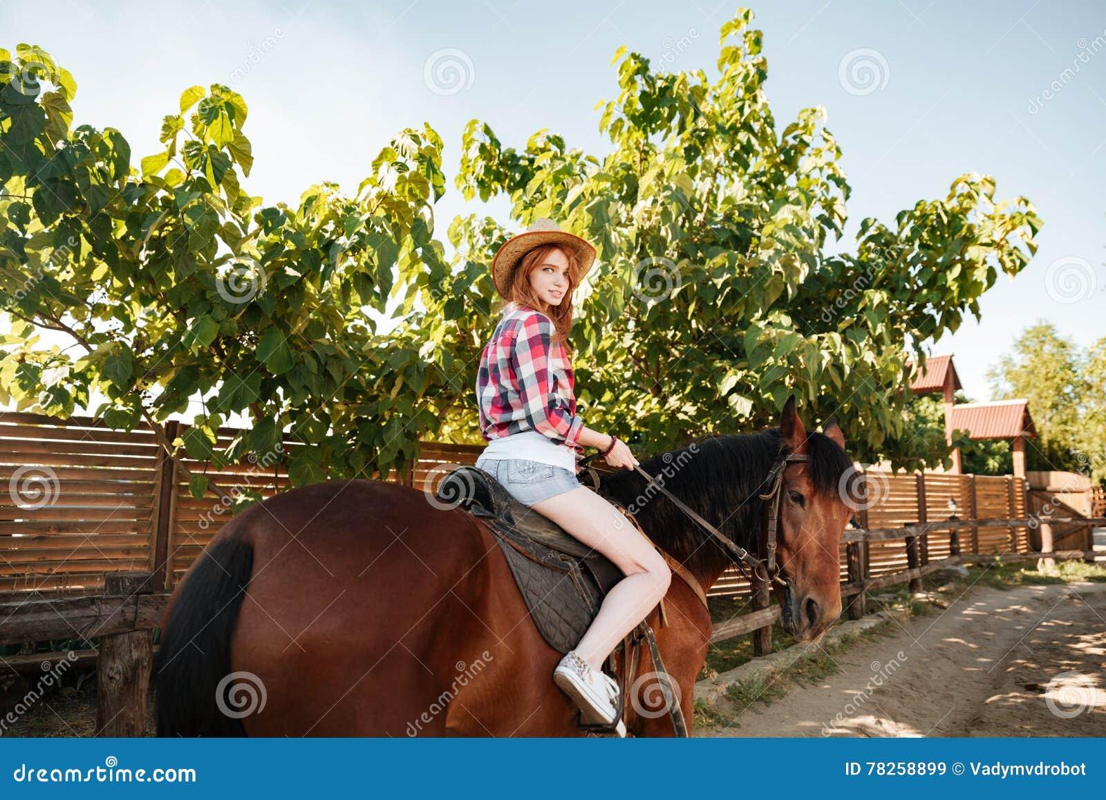 Όμορφο redhead νέο άλογο οδήγησης γυναικών cowgirl στο χωριό