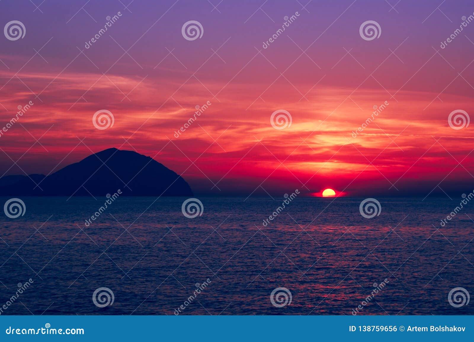 όμορφο seascape ηλιοβασίλεμα Διαποτισμένα χρώματα, σκιαγραφία ενός δύσκολου νησιού στη θάλασσα