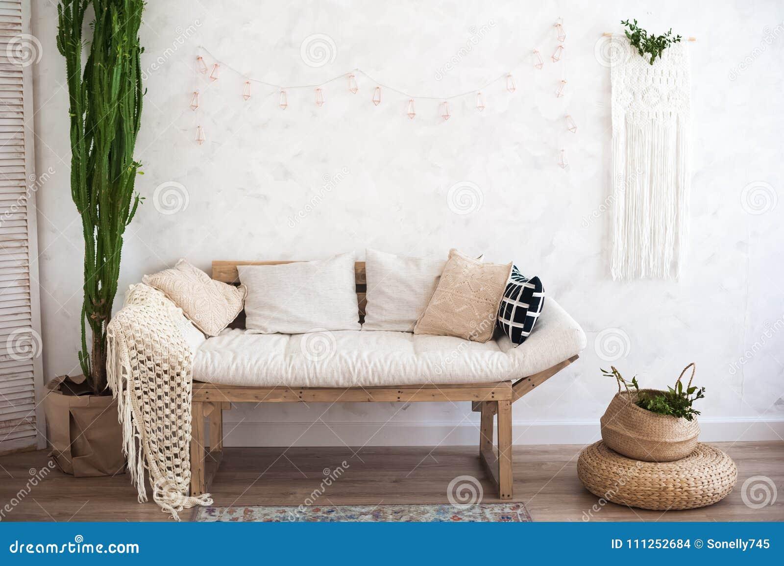 Όμορφο sping διακοσμημένο εσωτερικό στα άσπρα κατασκευασμένα χρώματα Καθιστικό, μπεζ καναπές με μια κουβέρτα και ένας μεγάλος κάκ