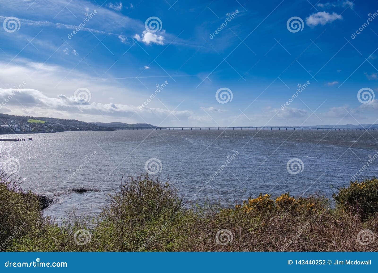 Όμορφο Tay και η γέφυρα ραγών Tay στο Dundee με σαφές μπλε Skys στη Σκωτία