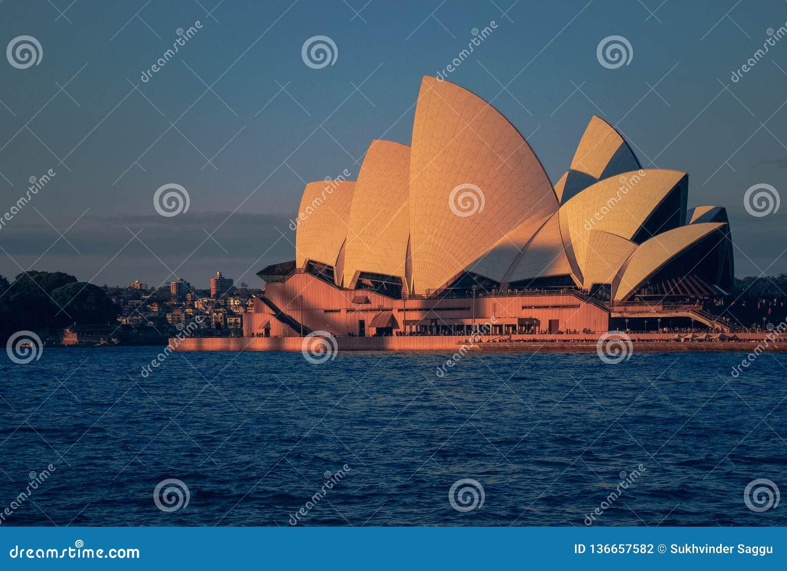 Όπερα κατά τη διάρκεια του ηλιοβασιλέματος που στέκεται στην μπλε ωκεάνια γραμμή ακτών και ουρανού στο Σίδνεϊ μια θερινή ημέρα
