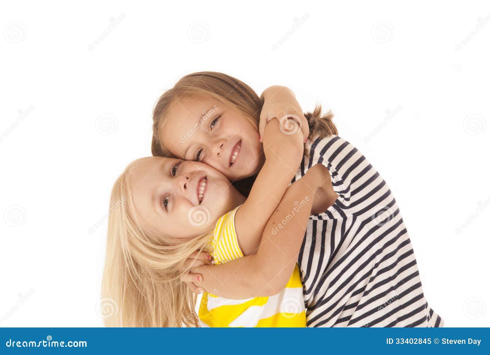 δύο νέες αδελφές που δίνουν ένα καθιστώντας προσφιλές αγκάλιασμα