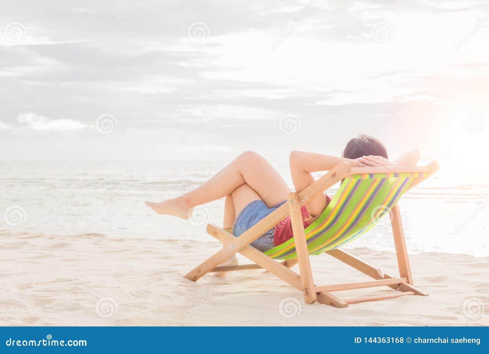 Ύπνος γυναικών στην καρέκλα παραλιών στη μεσημβρία