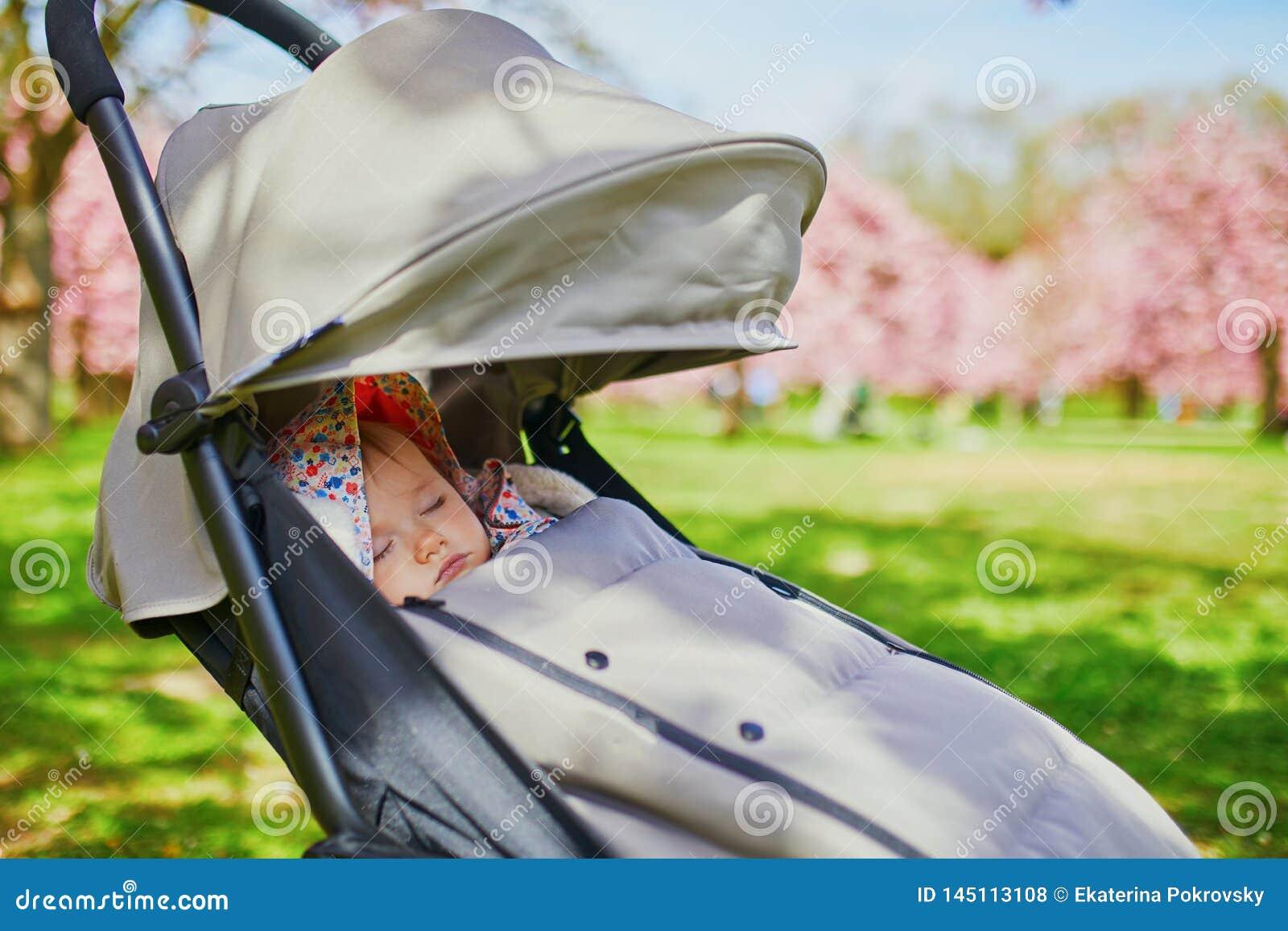 Ύπνος κοριτσάκι ενός έτους βρεφών στο καροτσάκι στο πάρκο