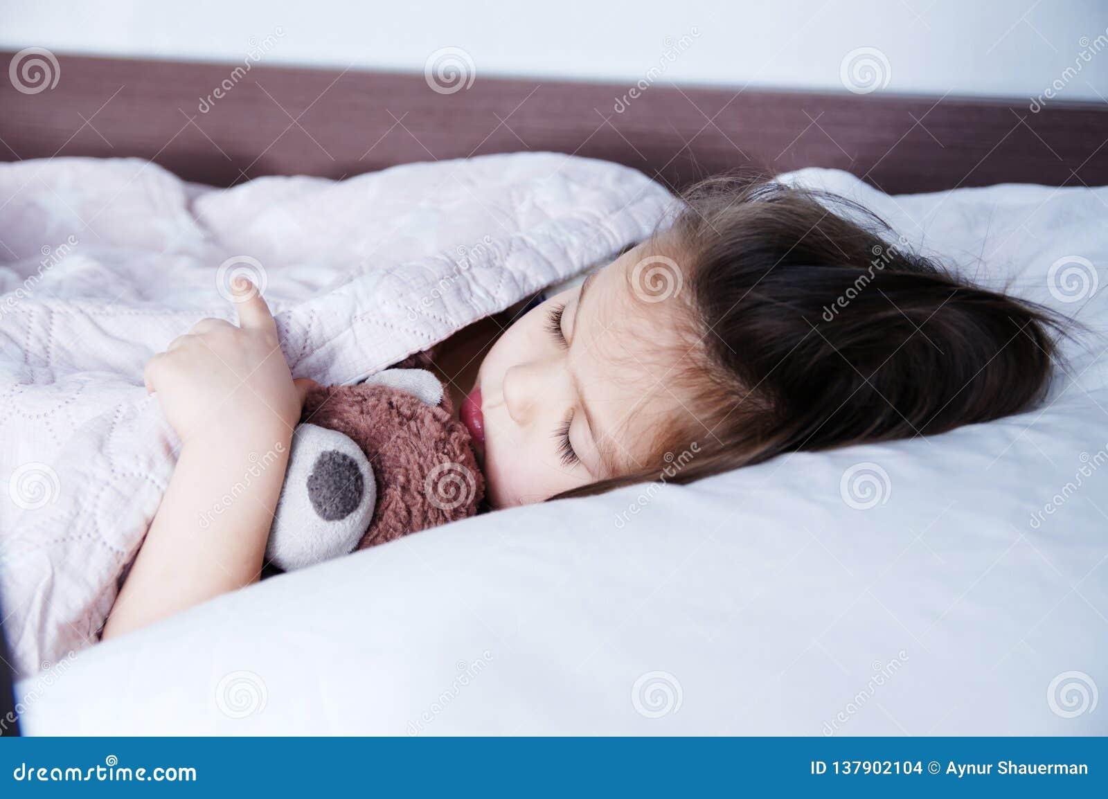 Ύπνος μικρών κοριτσιών που βρίσκεται στο κρεβάτι πρόγραμμα ύπνου στον εσωτερικό τρόπο ζωής χαριτωμένο παιδί με την αρκούδα