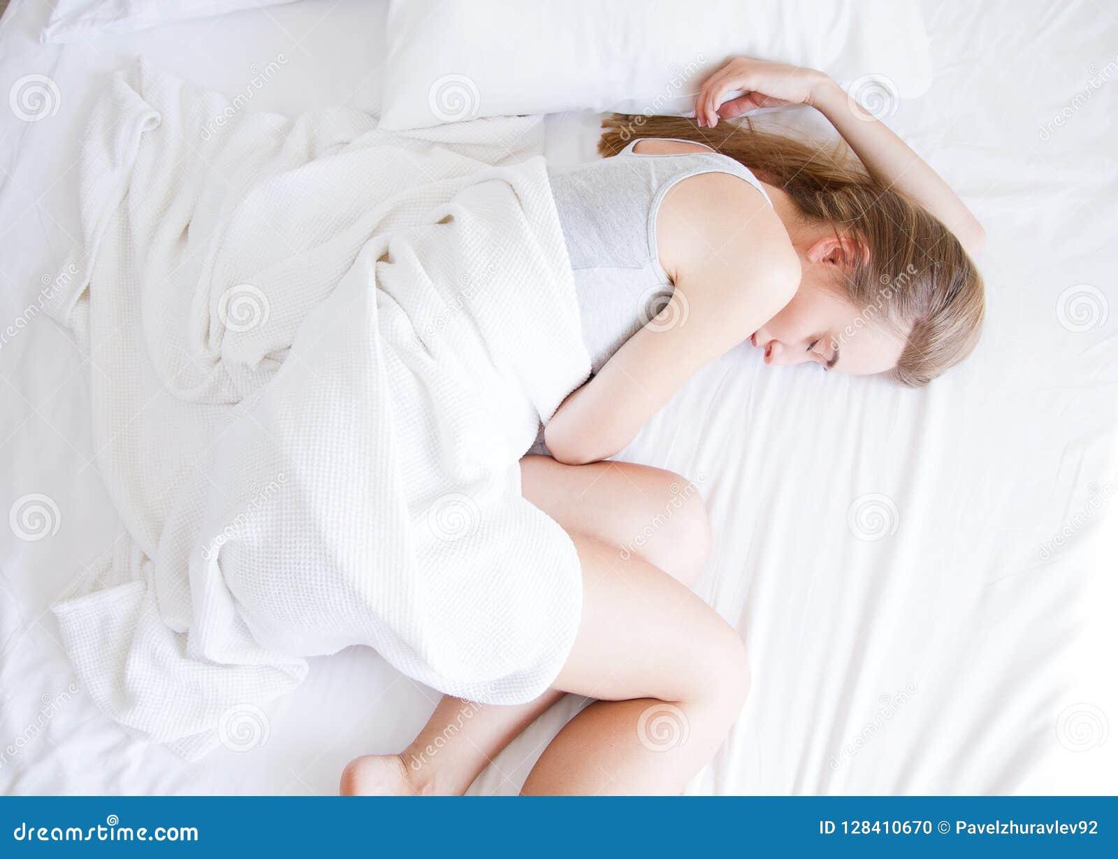ύπνος Νέος ύπνος γυναικών στο κρεβάτι, θηλυκό που στηρίζεται στο άνετο κρεβάτι με τα μαξιλάρια στην άσπρη κλινοστρωμνή στην ελαφρ