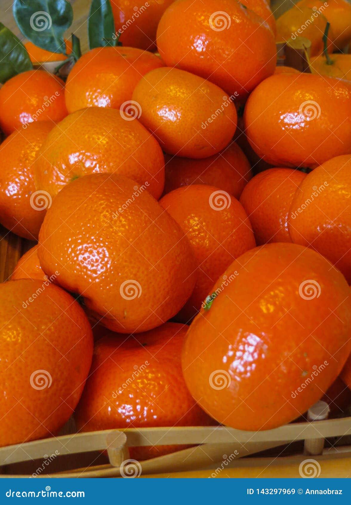 Ώριμα πορτοκαλιά μανταρίνια σε έναν ξύλινο δίσκο στον πίνακα