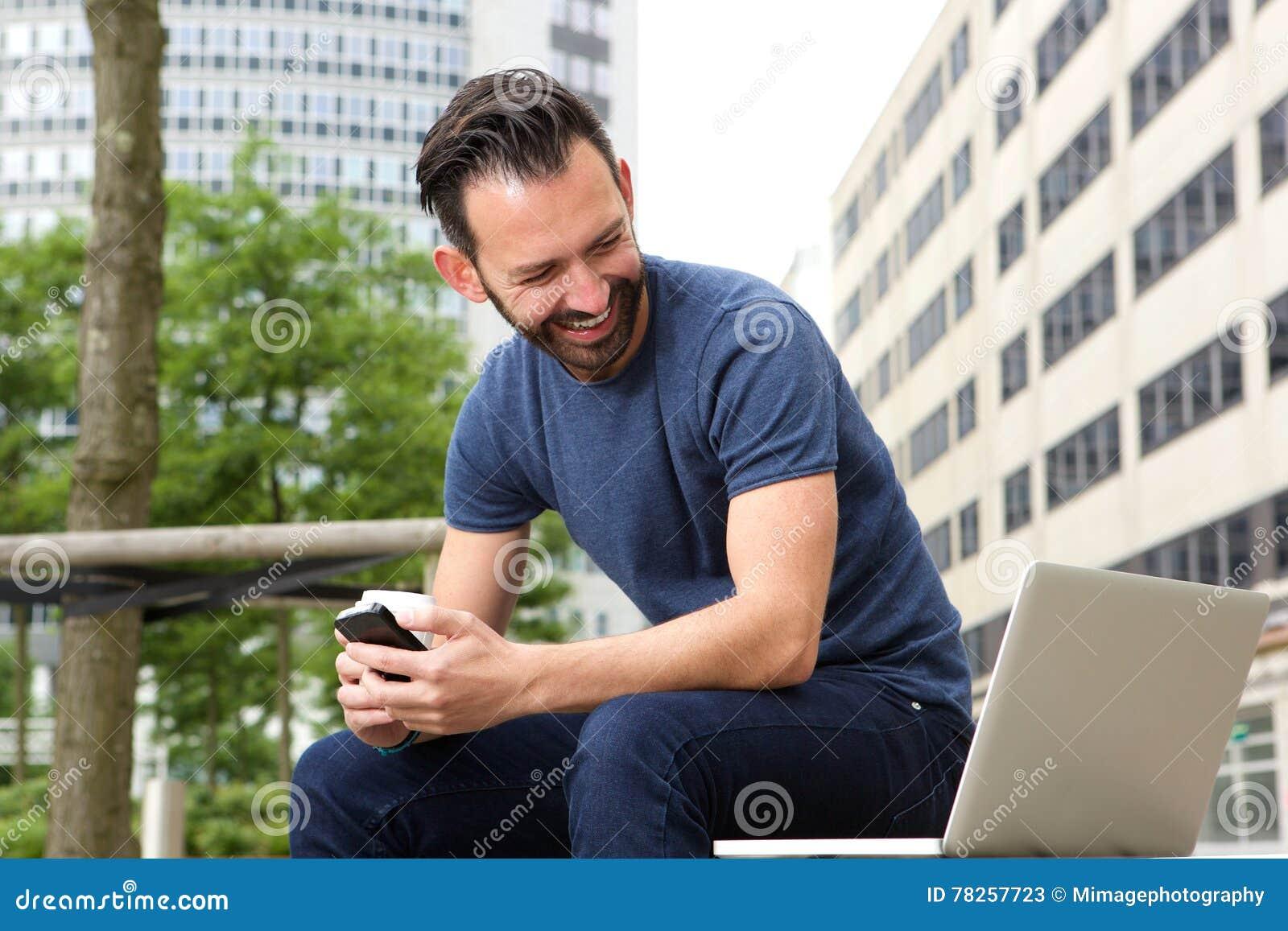 Ώριμη συνεδρίαση ατόμων που εξετάζει υπαίθρια το lap-top