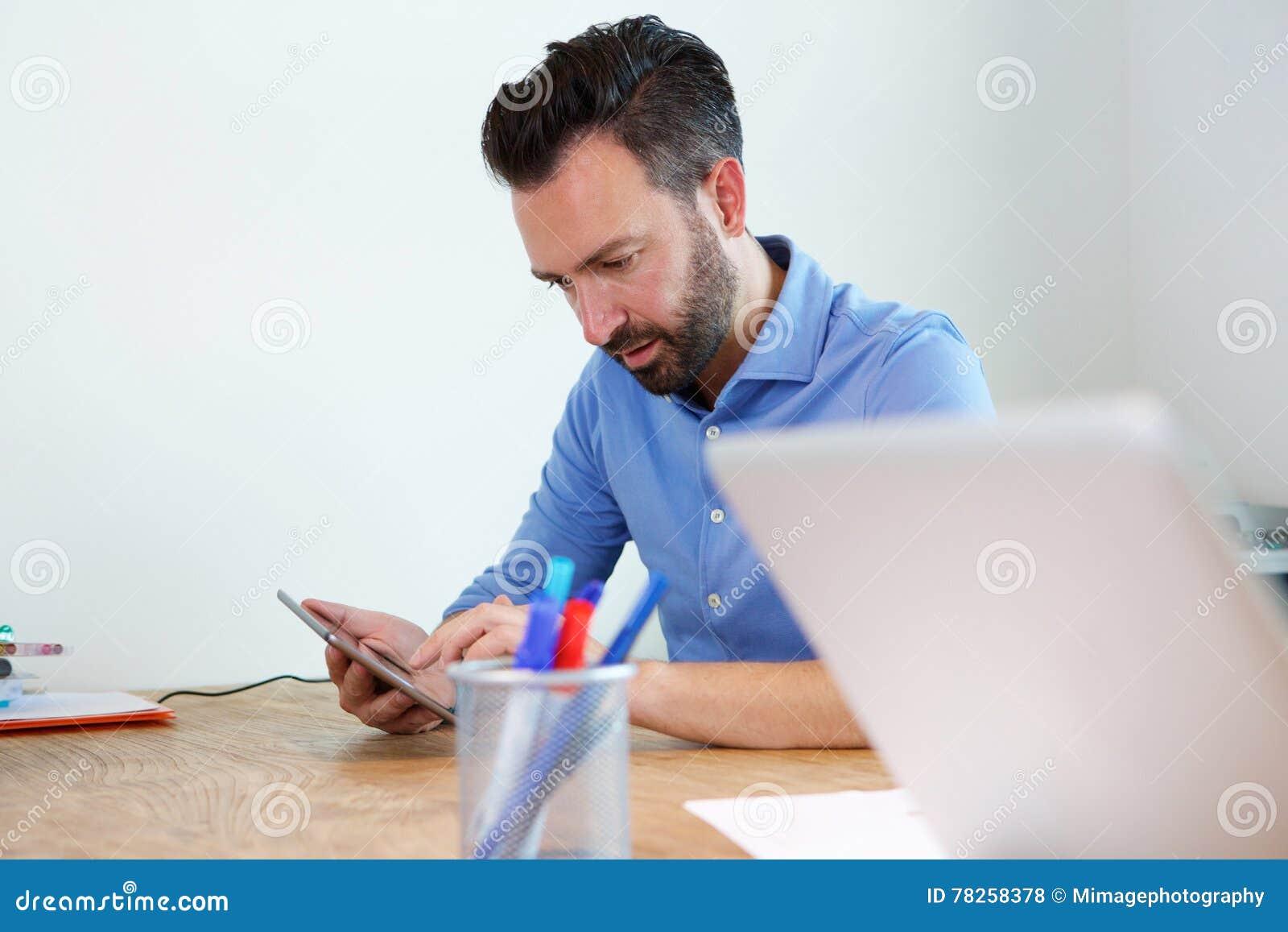 Ώριμη συνεδρίαση επιχειρησιακών ατόμων στο γραφείο του που χρησιμοποιεί την ψηφιακή ταμπλέτα