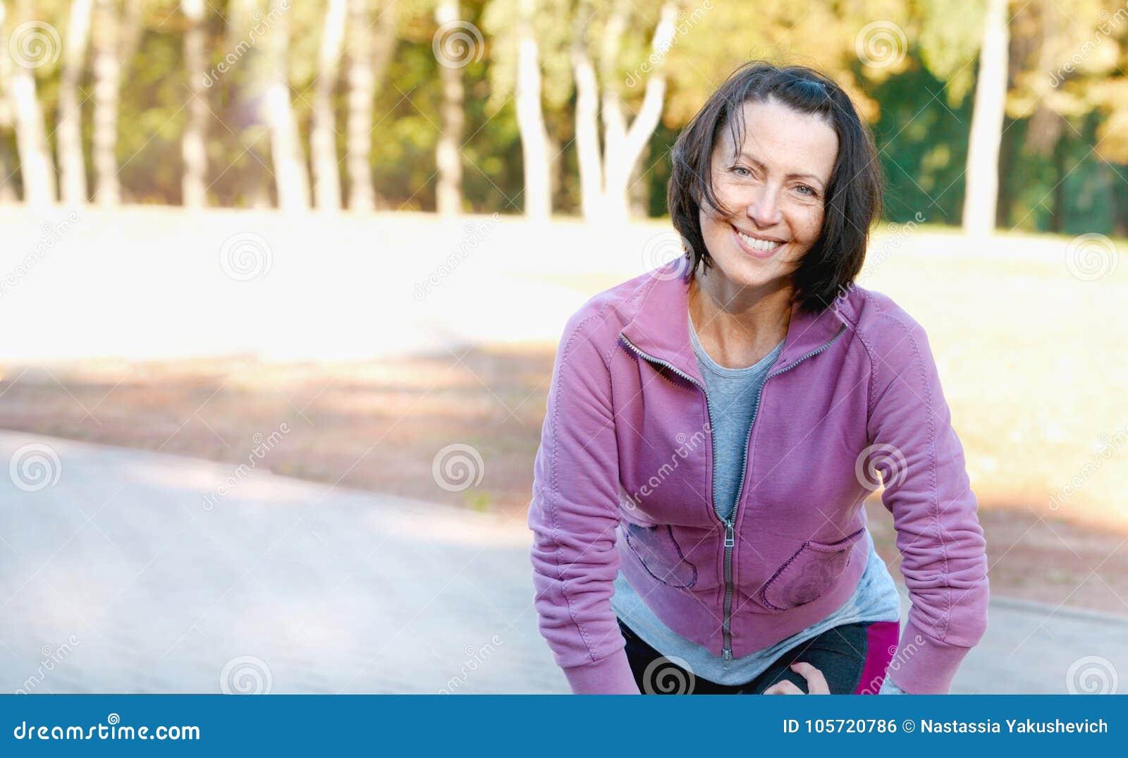 Ώριμος δρομέας γυναικών που παίρνει ένα υπόλοιπο μετά από να τρέξει στο πάρκο