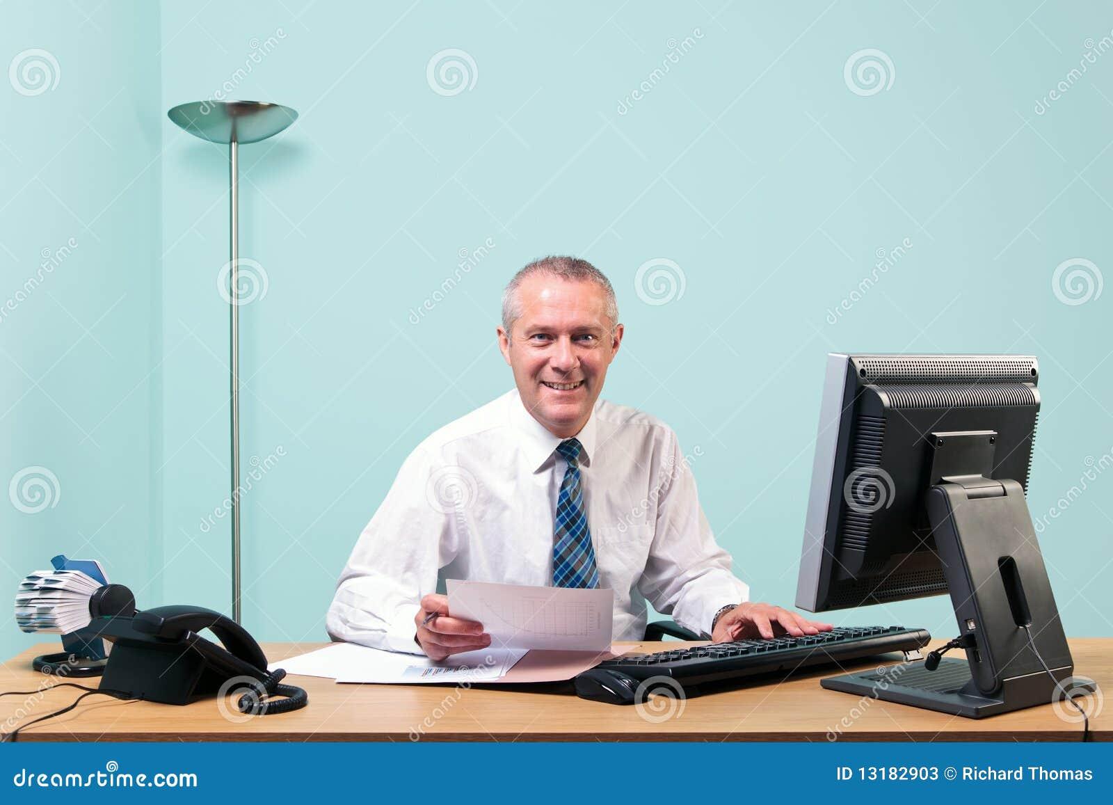 Ώριμος επιχειρηματίας που κάθεται στο γραφείο γραφείων του