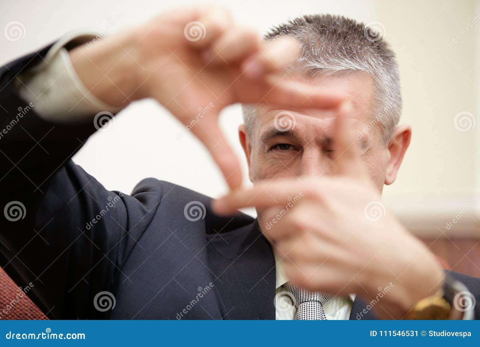 Ώριμος επιχειρηματίας που κοιτάζει μέσω του τετραγωνικού πλαισίου που κάνει από το δάχτυλο
