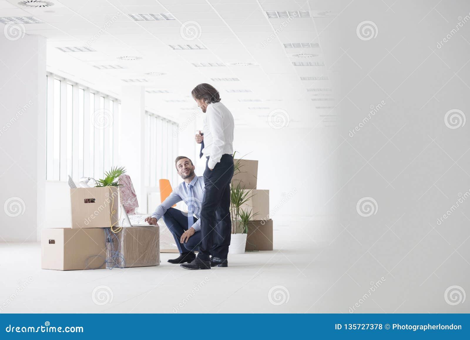 Ώριμος επιχειρηματίας που μιλά στο νέο σκύψιμο συναδέλφων από τα κουτιά από χαρτόνι στο νέο γραφείο