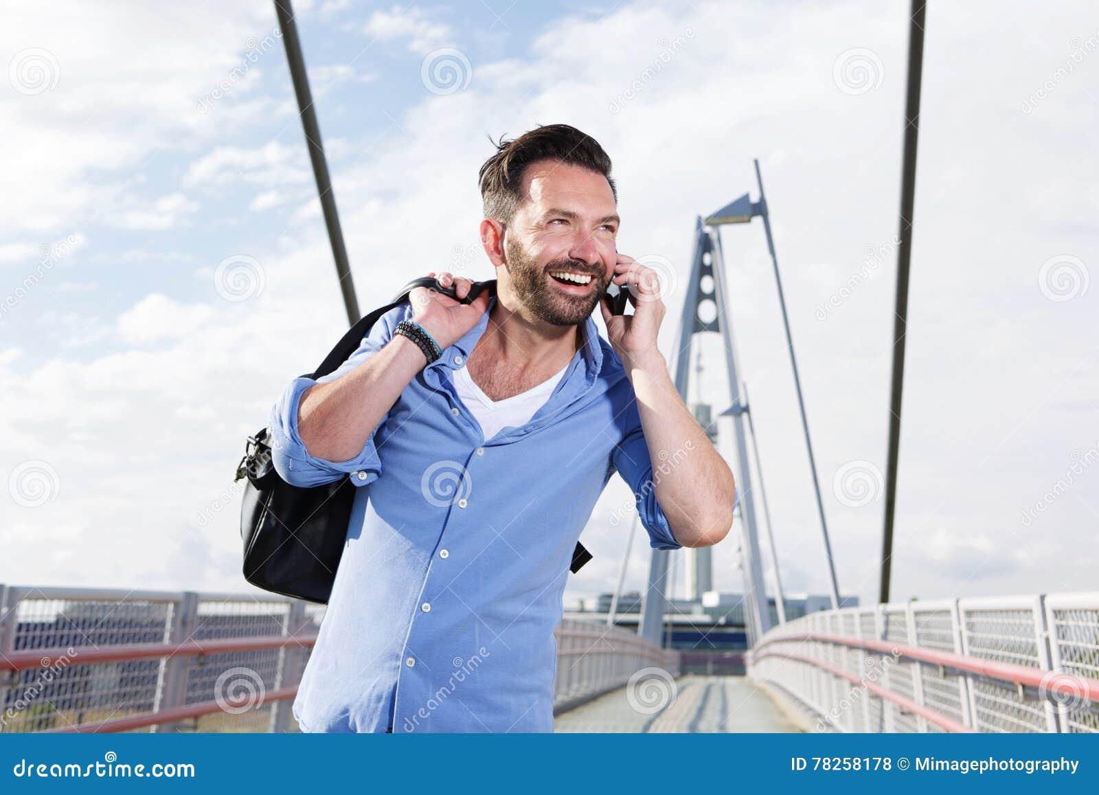 Ώριμο άτομο με την τσάντα που μιλά στο κινητό τηλέφωνο και το γέλιο