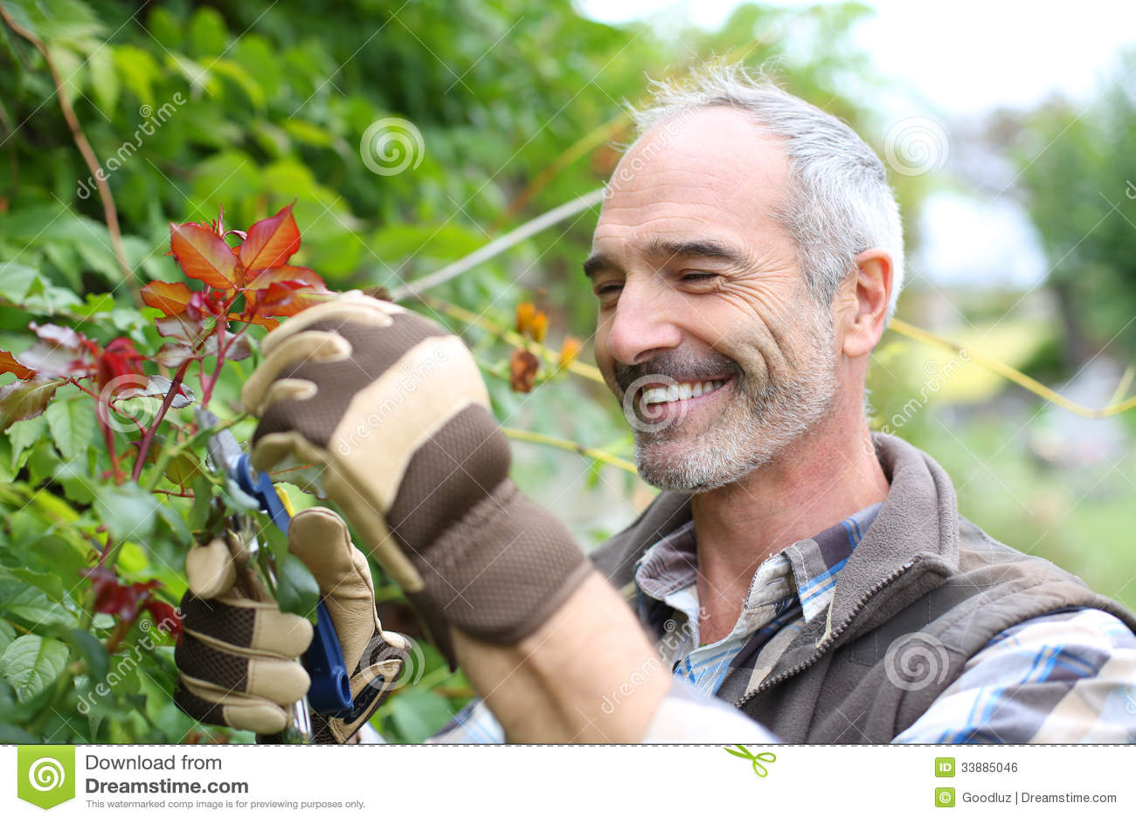 Ώριμο άτομο στον κήπο με τα γάντια και τις ψαλίδες