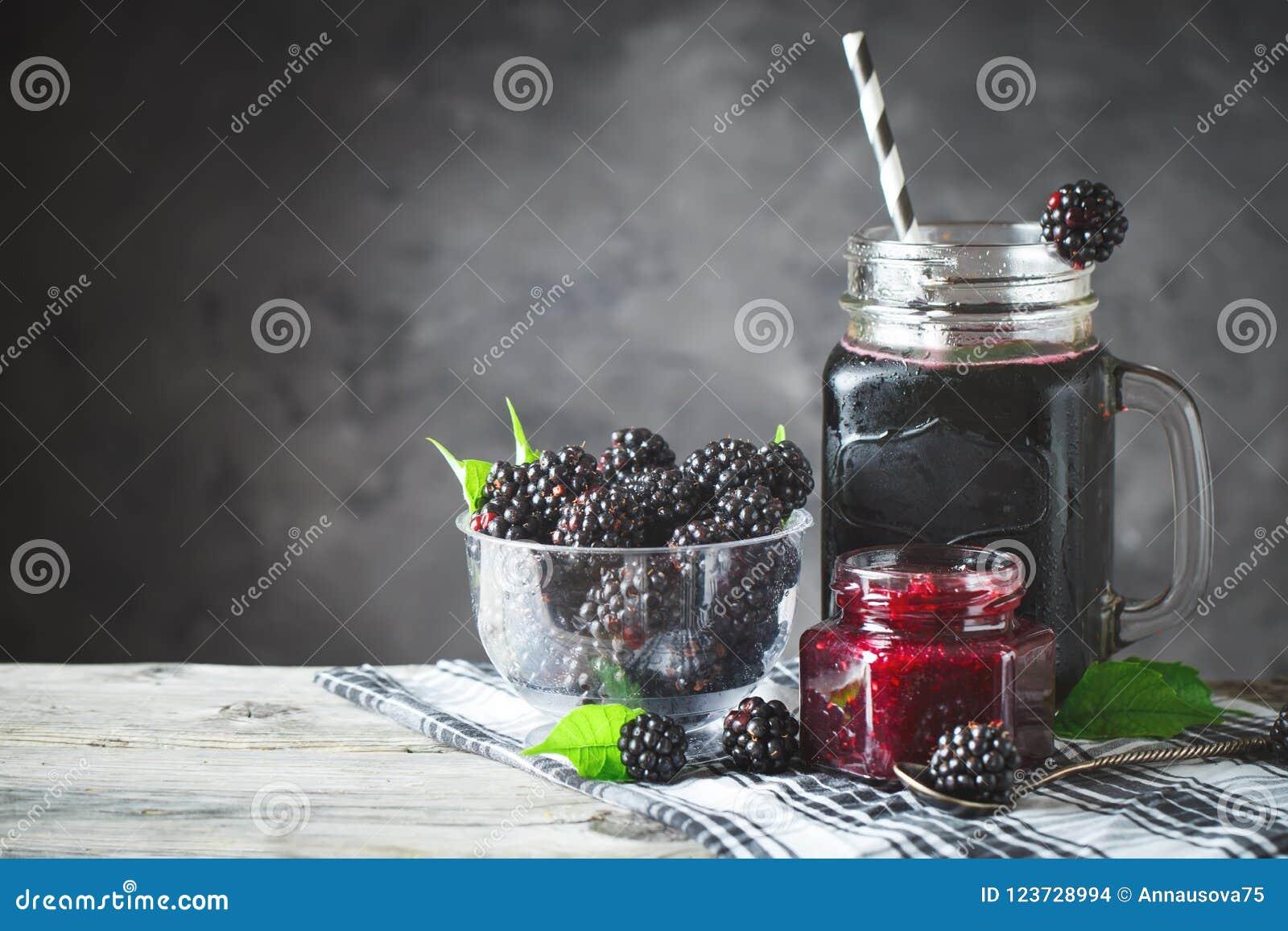 Ώριμο βατόμουρο, χυμός βατόμουρων και μαρμελάδα σε έναν ξύλινο πίνακα Σκοτεινή ανασκόπηση