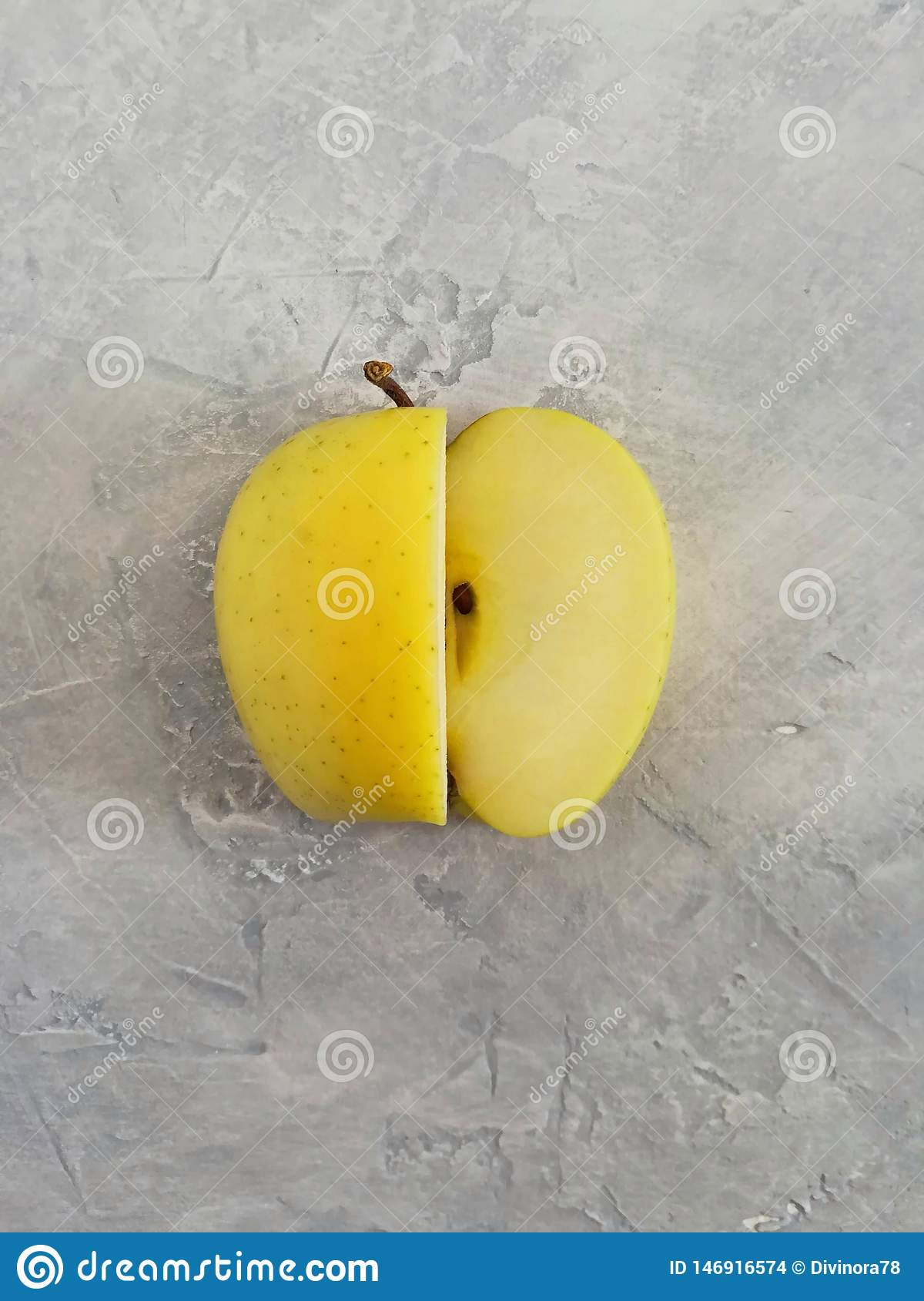 Ώριμο κίτρινο μήλο σε ένα γκρίζο συγκεκριμένο υπόβαθρο