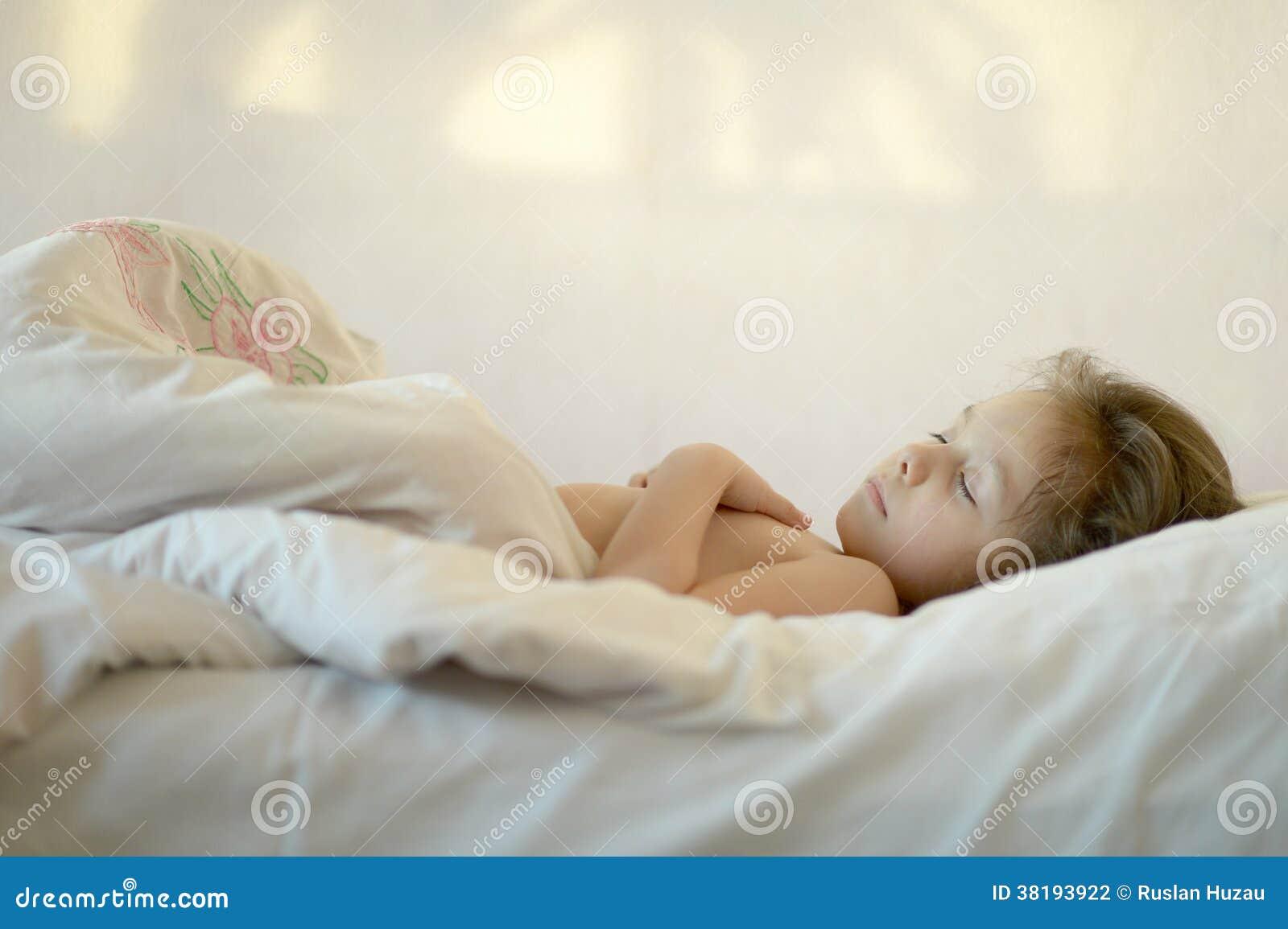 睡觉在一张床上的逗人喜爱的小女孩早晨