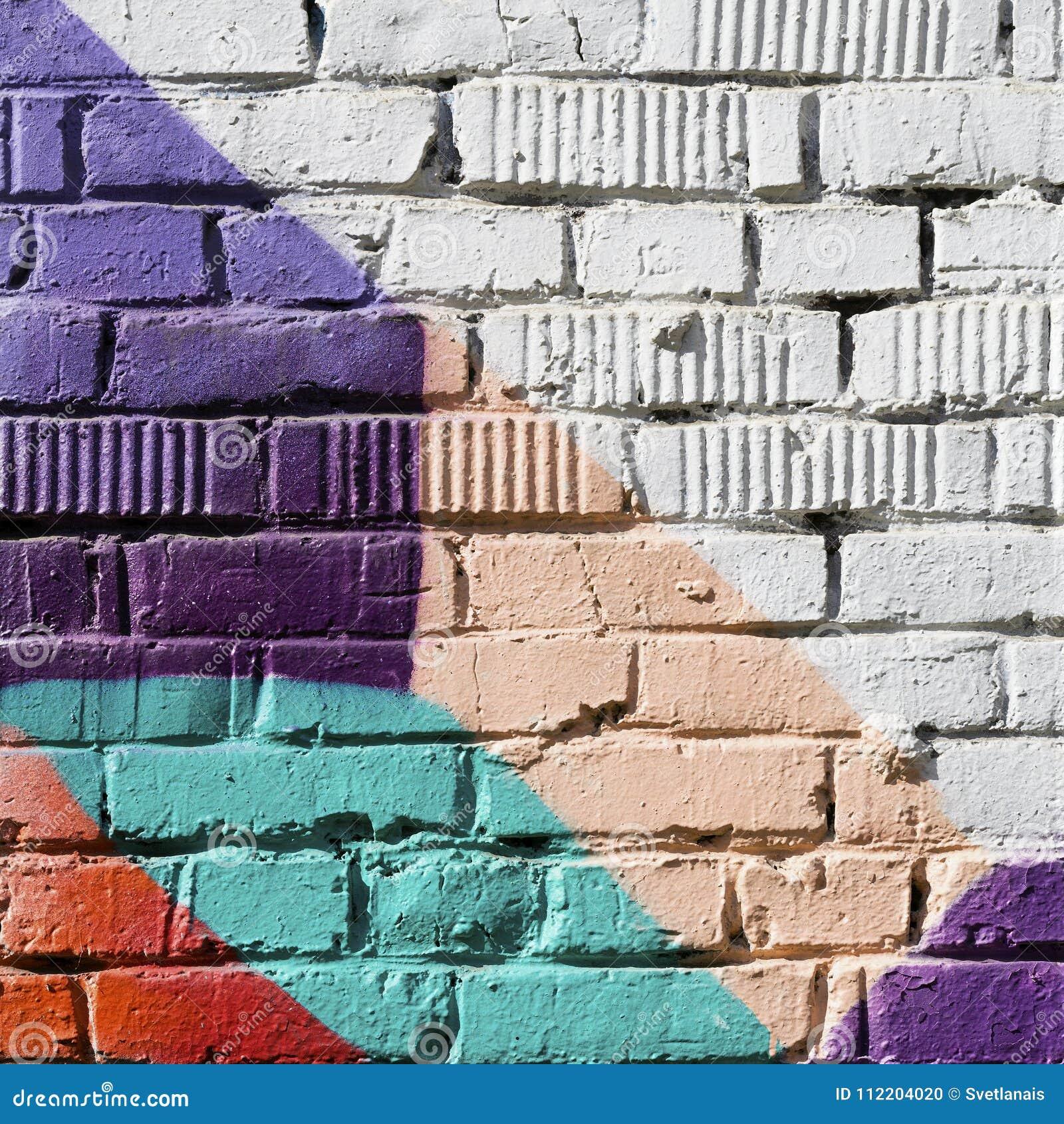 Абстрактная деталь кирпичной стены с частью красочных граффити Городской конец-вверх искусства С местом для вашего текста, для
