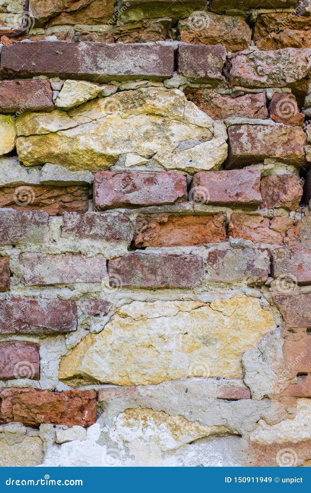Абстрактные предпосылки: старая загубленная красная кирпичная стена с камнями известки