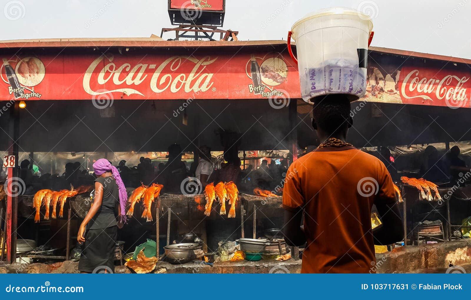АБУДЖА, НИГЕРИЯ, АФРИКА - 3-ЬЕ МАРТА 2014: Неопознанный африканский человек балансируя пластичное ведро на рыбном базаре Абуджи