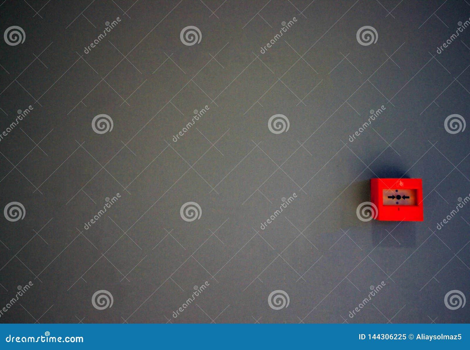 Аварийный переключатель огня или кнопка помещенные на серой стене, автоматизация спасения, огонь колокол