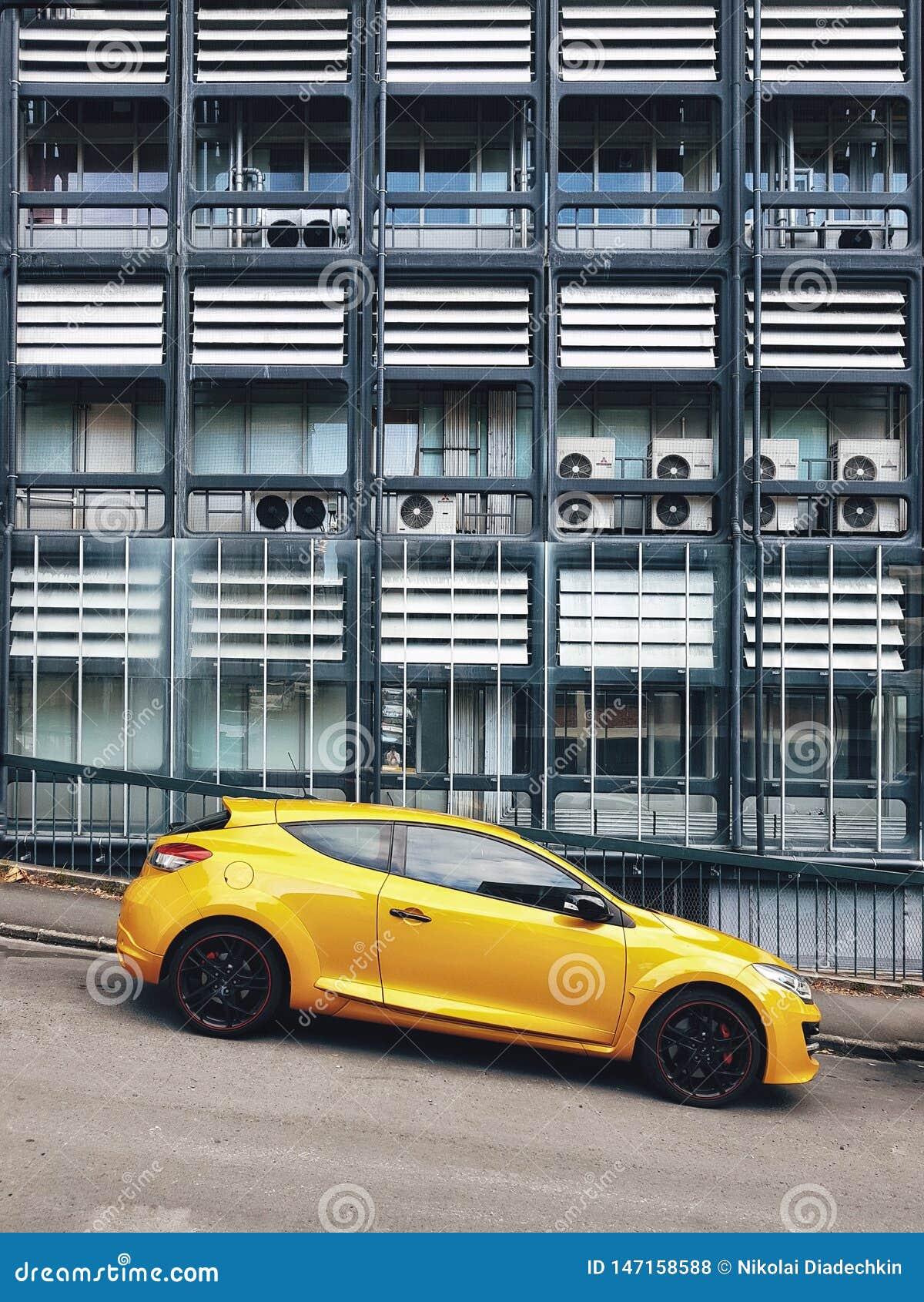Автомобили припаркованные на дороге против предпосылки современного здания