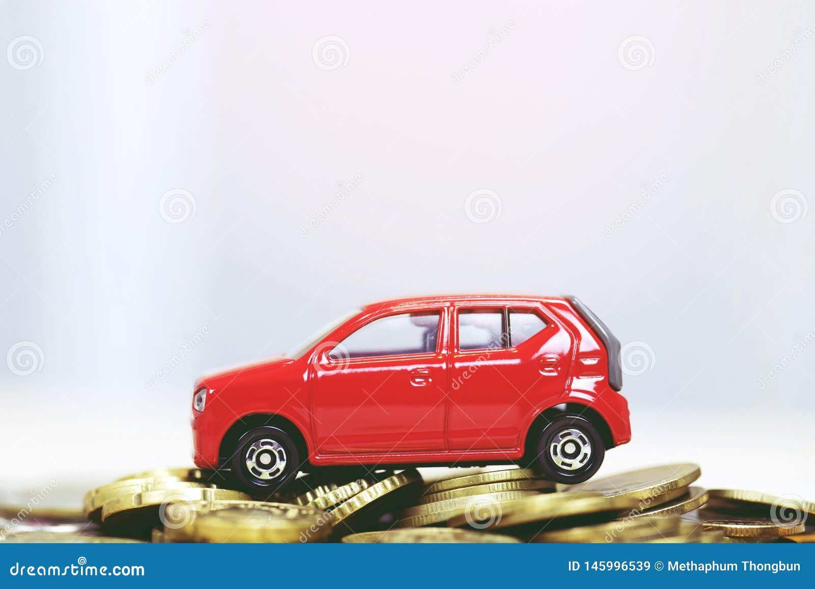 Автомобиль маленькой игрушки красный над много монетками штабелированными деньгами для банковских ссуд стоит финансы