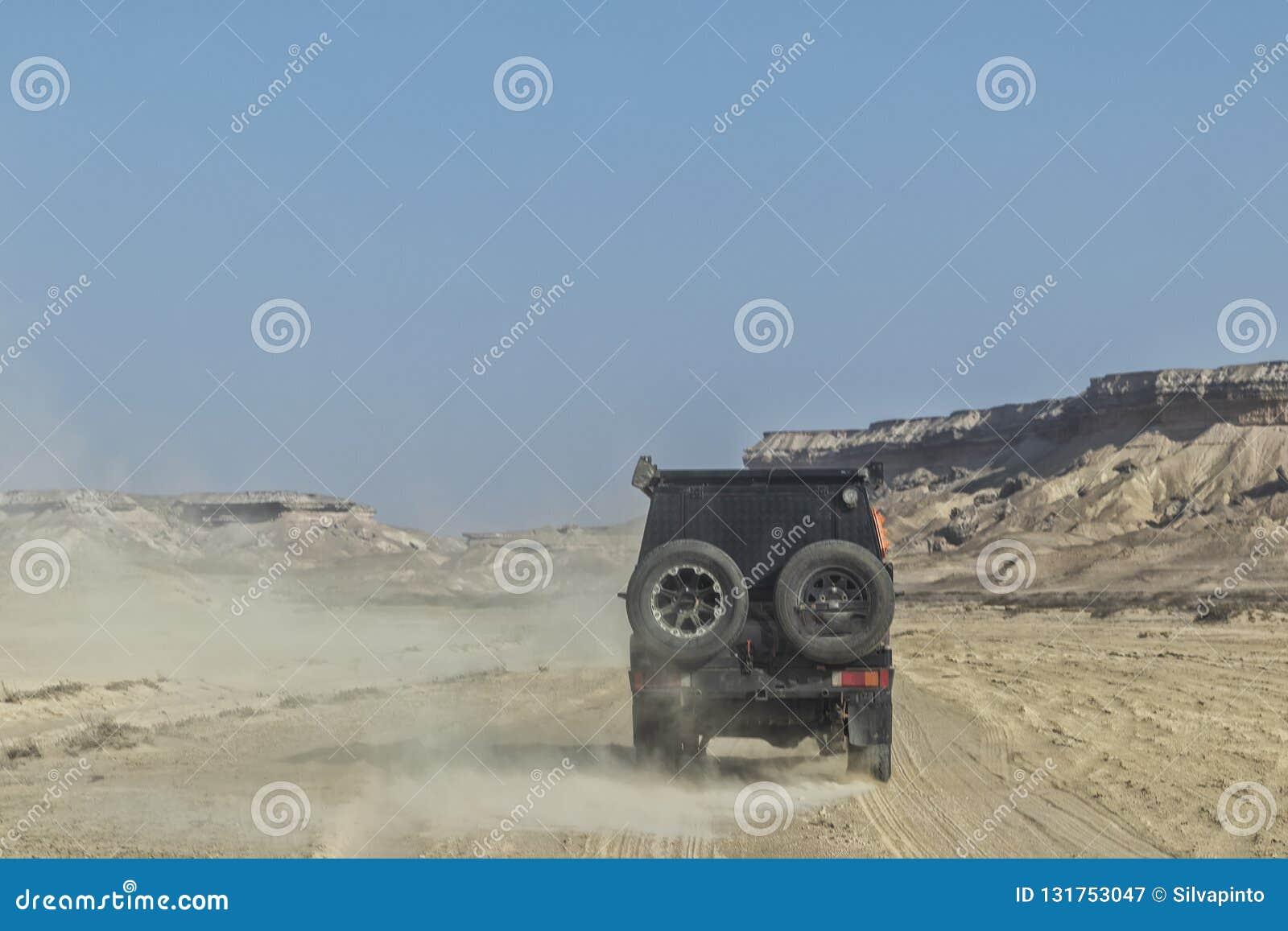 автомобиль 4x4 на дороге песка в каньонах пустыни Namibe вышесказанного anisette